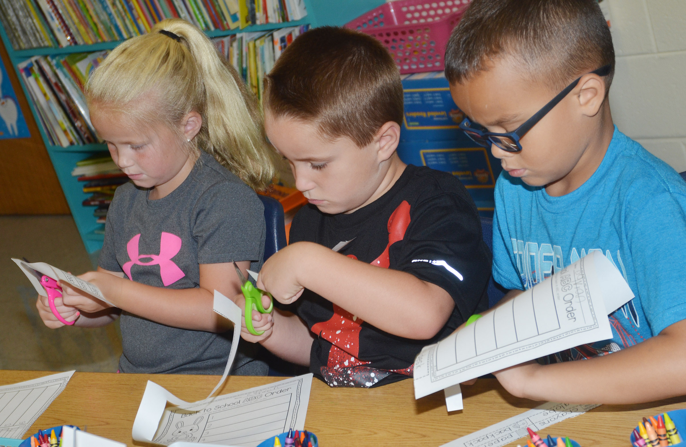 CES first-graders, from left, Lillie Judd, Kaiden Bradfield and Davian Taylor cut out the words on their worksheets.