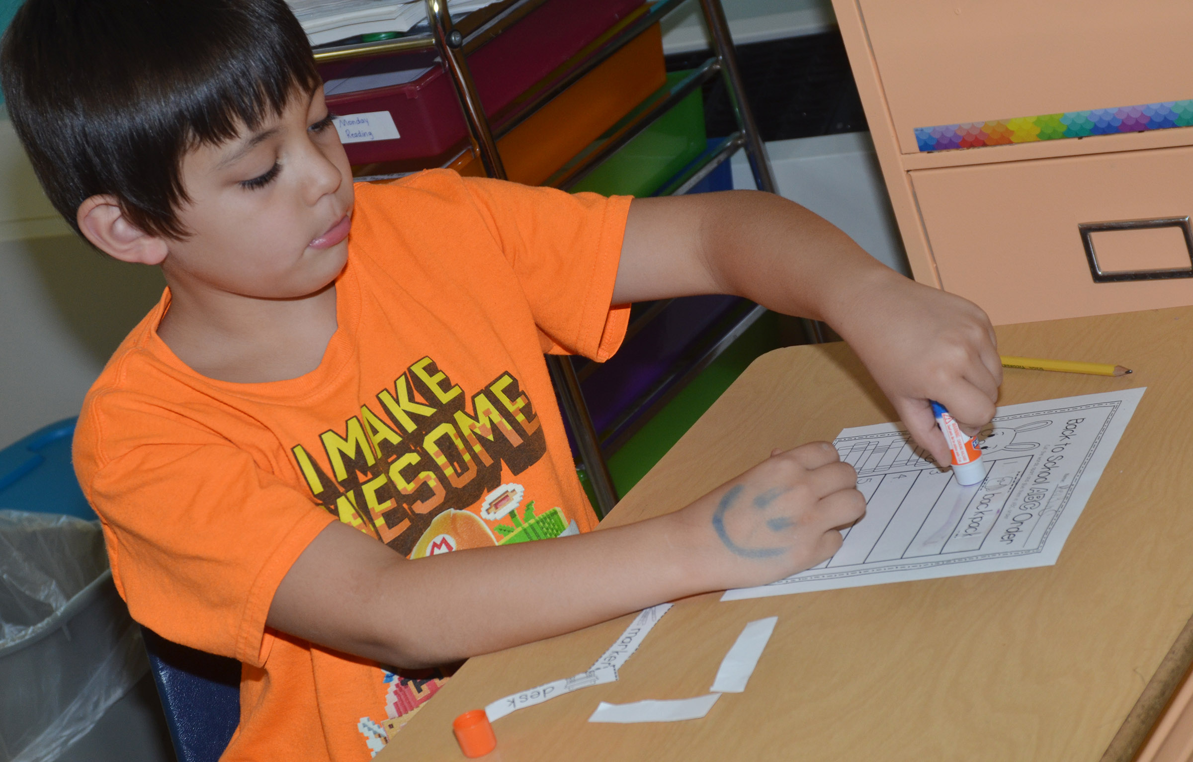 CES first-grader Keagan Shearer glues his words in alphabetical order.