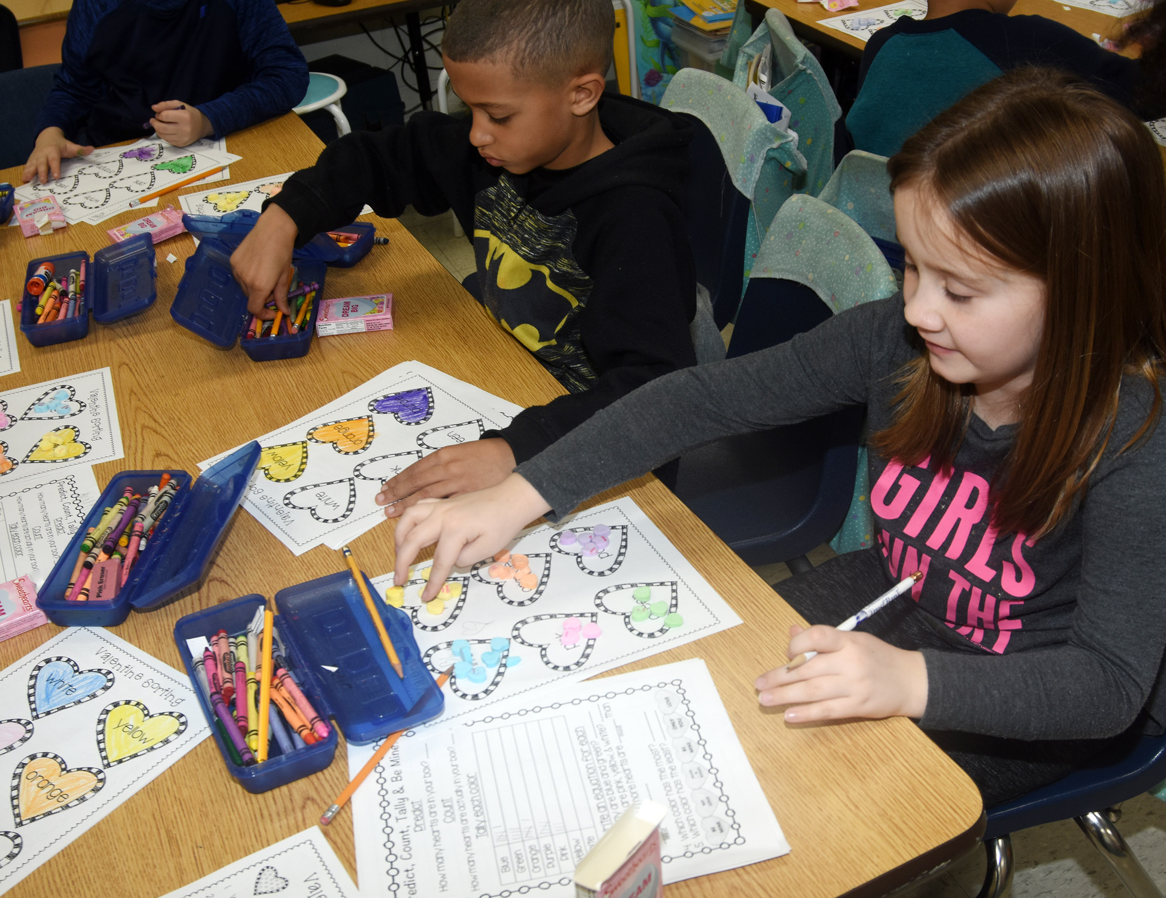 CES first-graders Tyce Owens, at left, and Natalee Shaw sort their hearts.