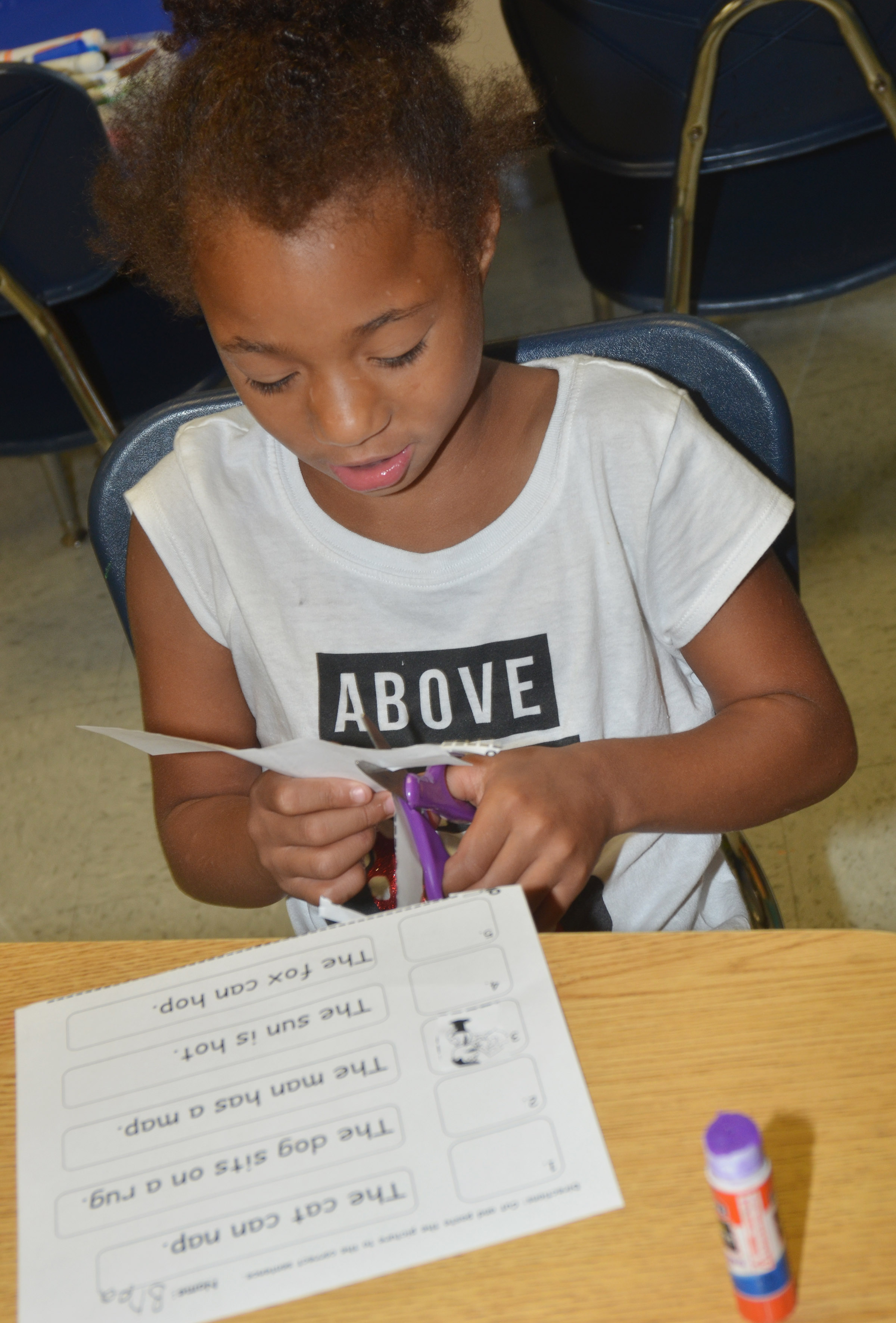 CES first-grader Brea Miller cuts out the pictures on her worksheet.