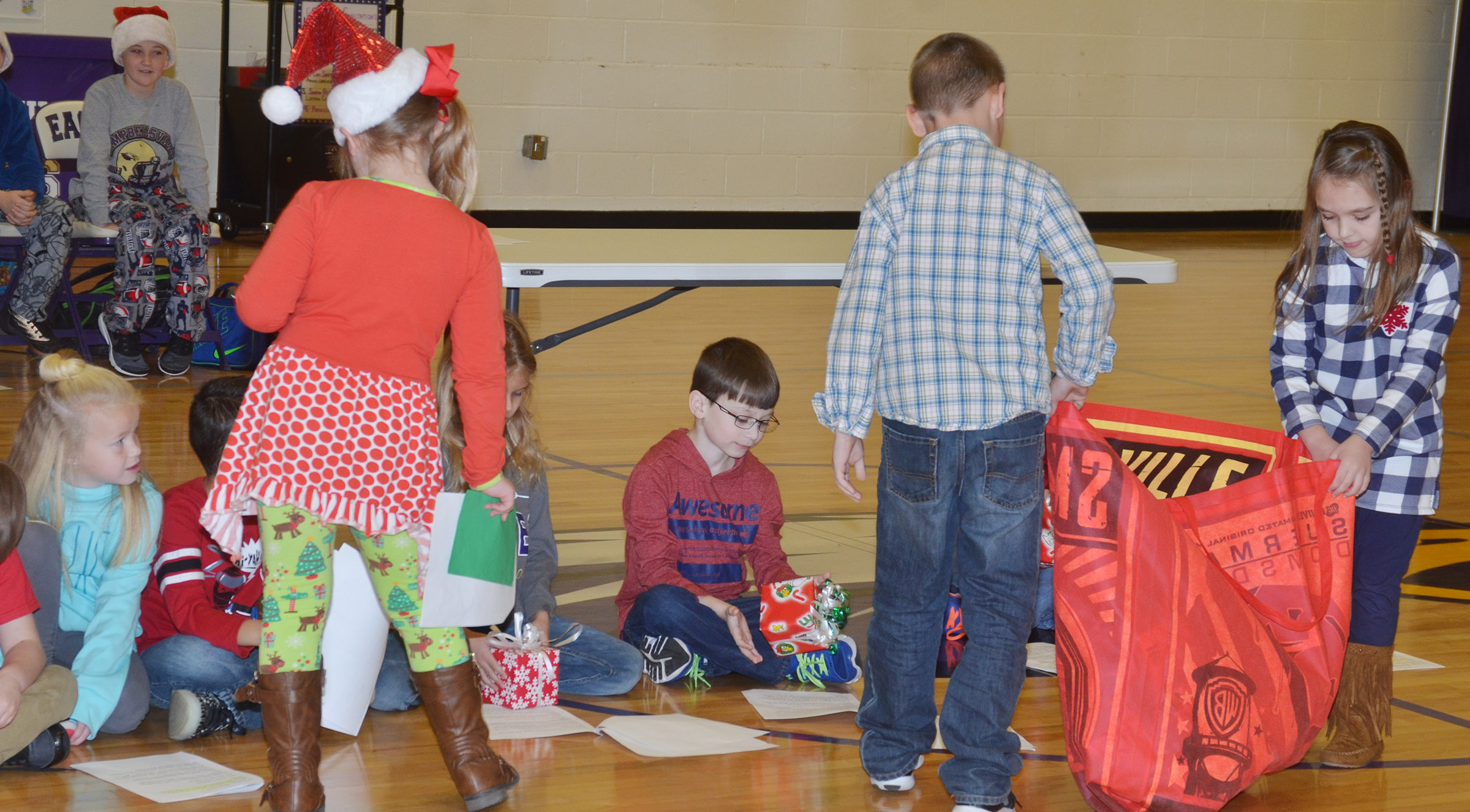 CES first-graders Aubreigh Knifley, at left, and Braxton Rhodes pass out gifts as they portray Santa and the school principal.