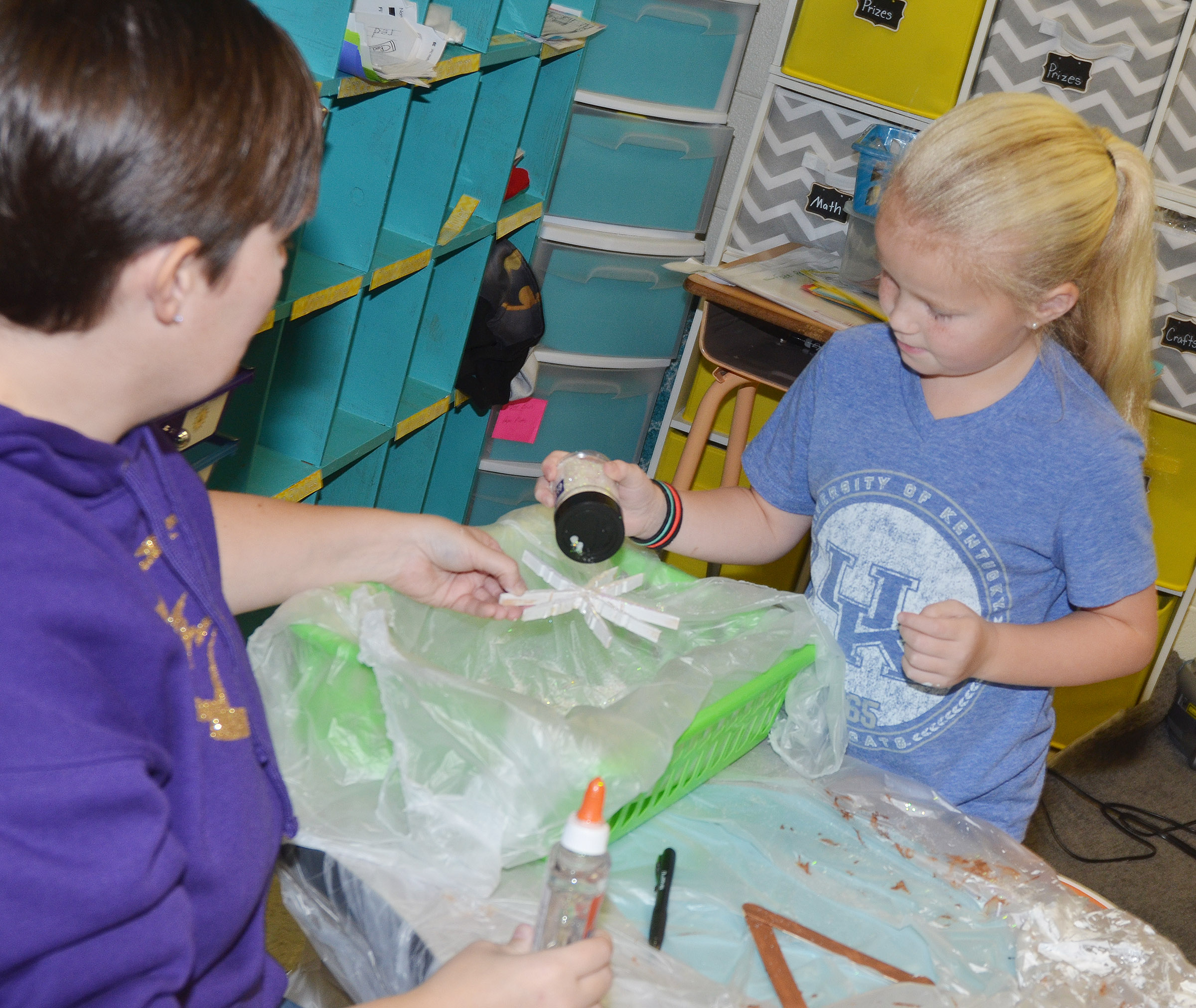 CES first-grader Lillie Judd adds glitter to her snowflake ornament.