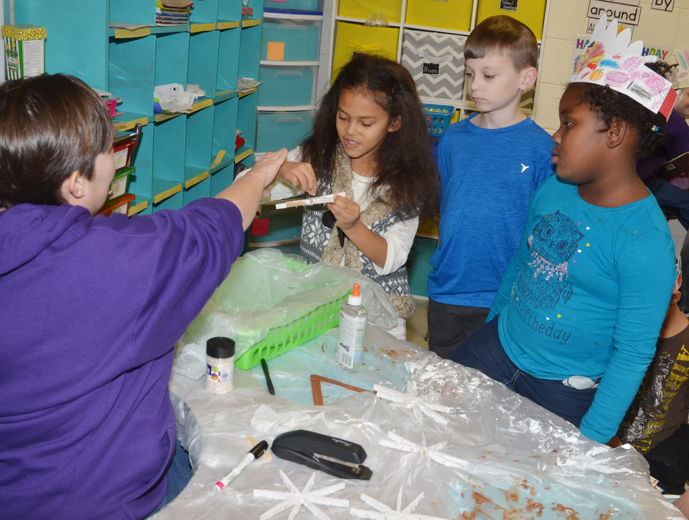 CES first-grader Marlee Dickens adds glitter to her snowflake ornament, with some help from her teacher Amanda Barnett. At right, first-graders Parker Newton and Destinee Henry-Turner wait their turn.