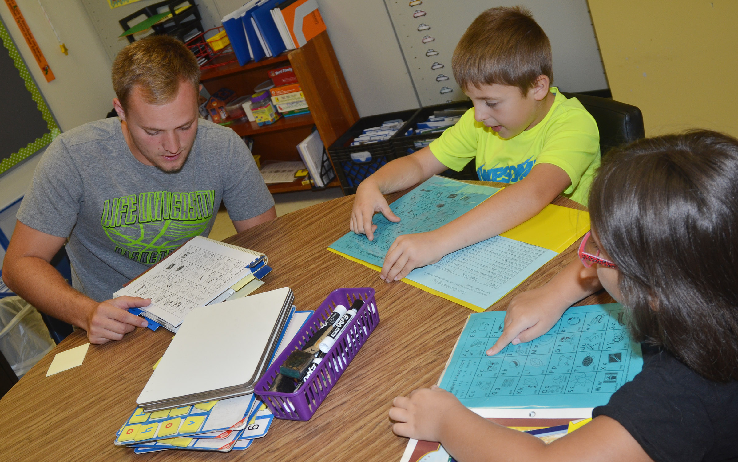 CES AmeriCorps tutor Bradley Bates recites the alphabet with first-graders Ayden Andrew and Hannah Matias.