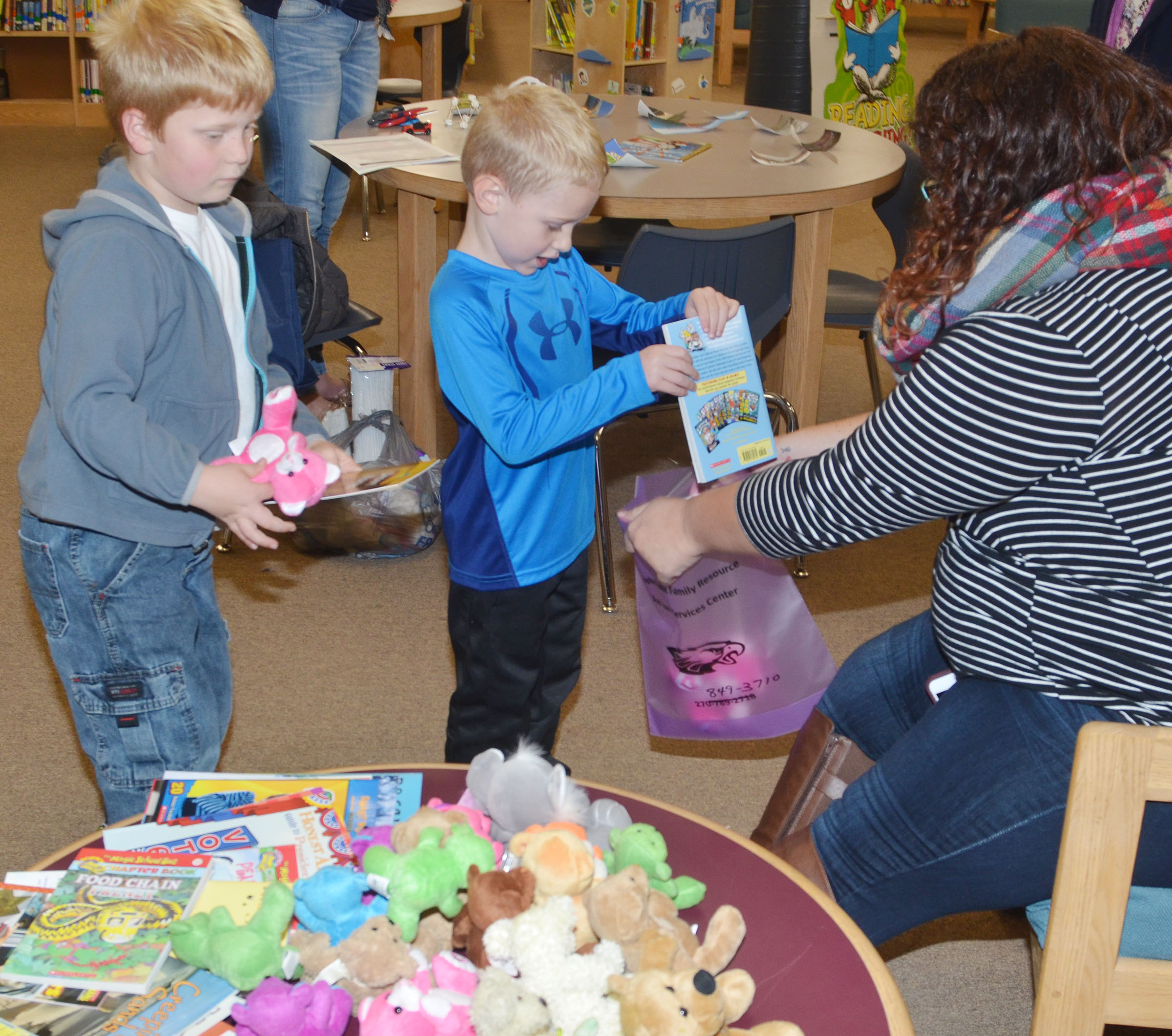 Lydia Rakes, who works with AmeriCorps at CES, helps first-grader Ben Parrott, at left, and kindergartener Jackson Wright choose their book and teddy bear.