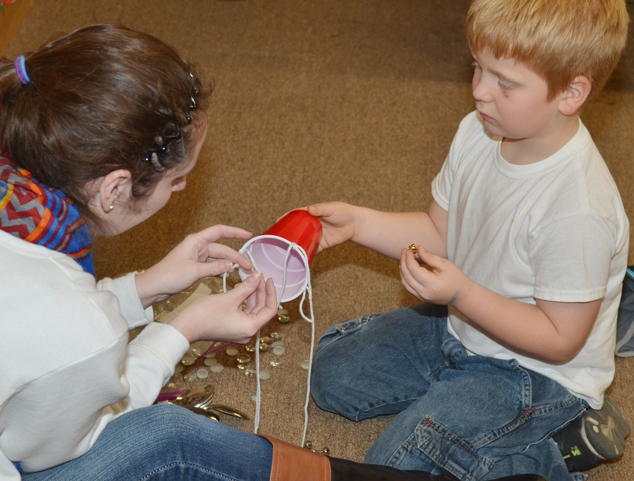 CES first-grader Ben Parrott makes a wind chime with CU early childhood education student Cassie Emery.