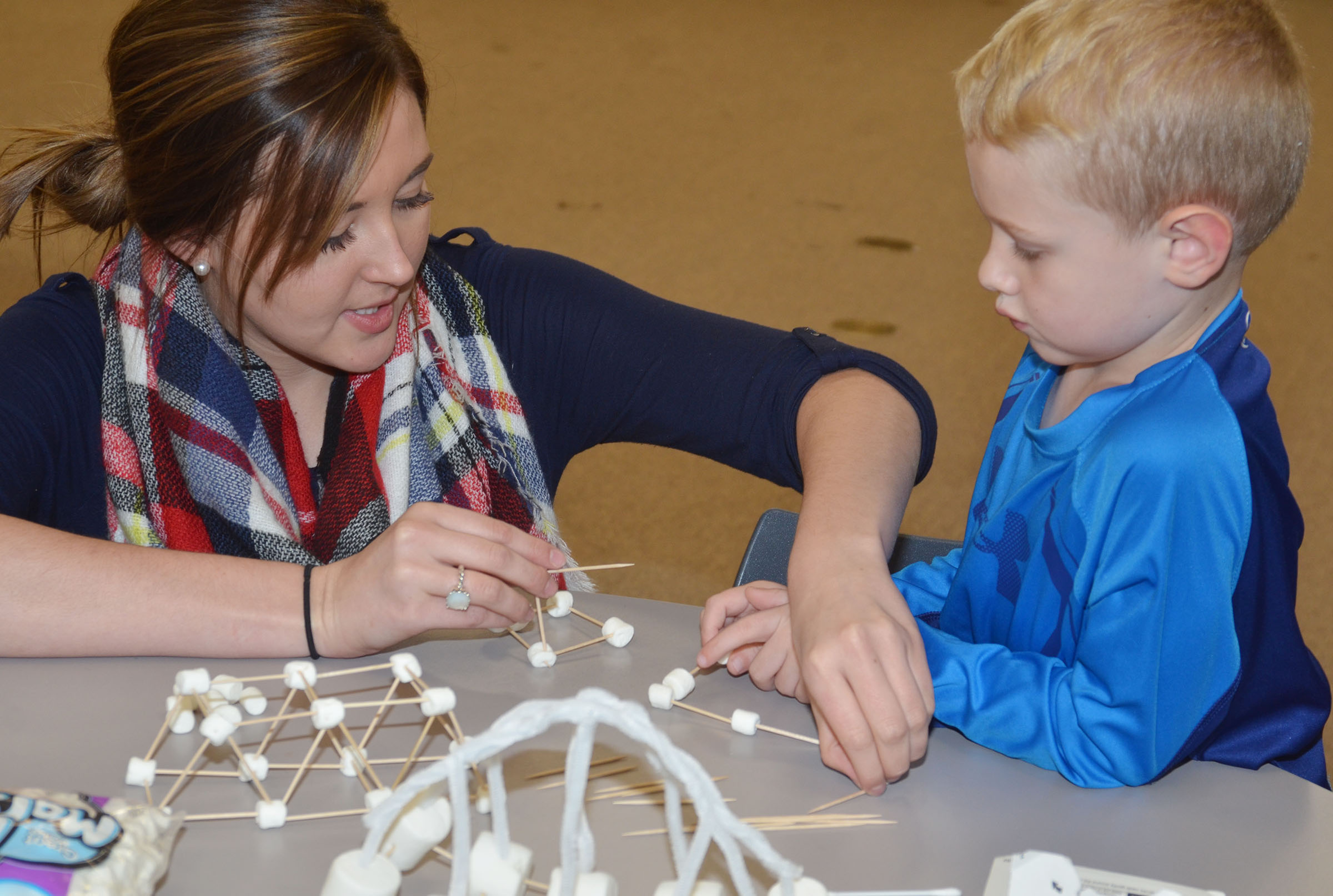 CU early childhood education student Lindsey Browning helps CES kindergartener Jackson Wright make a bridge out of marshmallows and toothpicks.