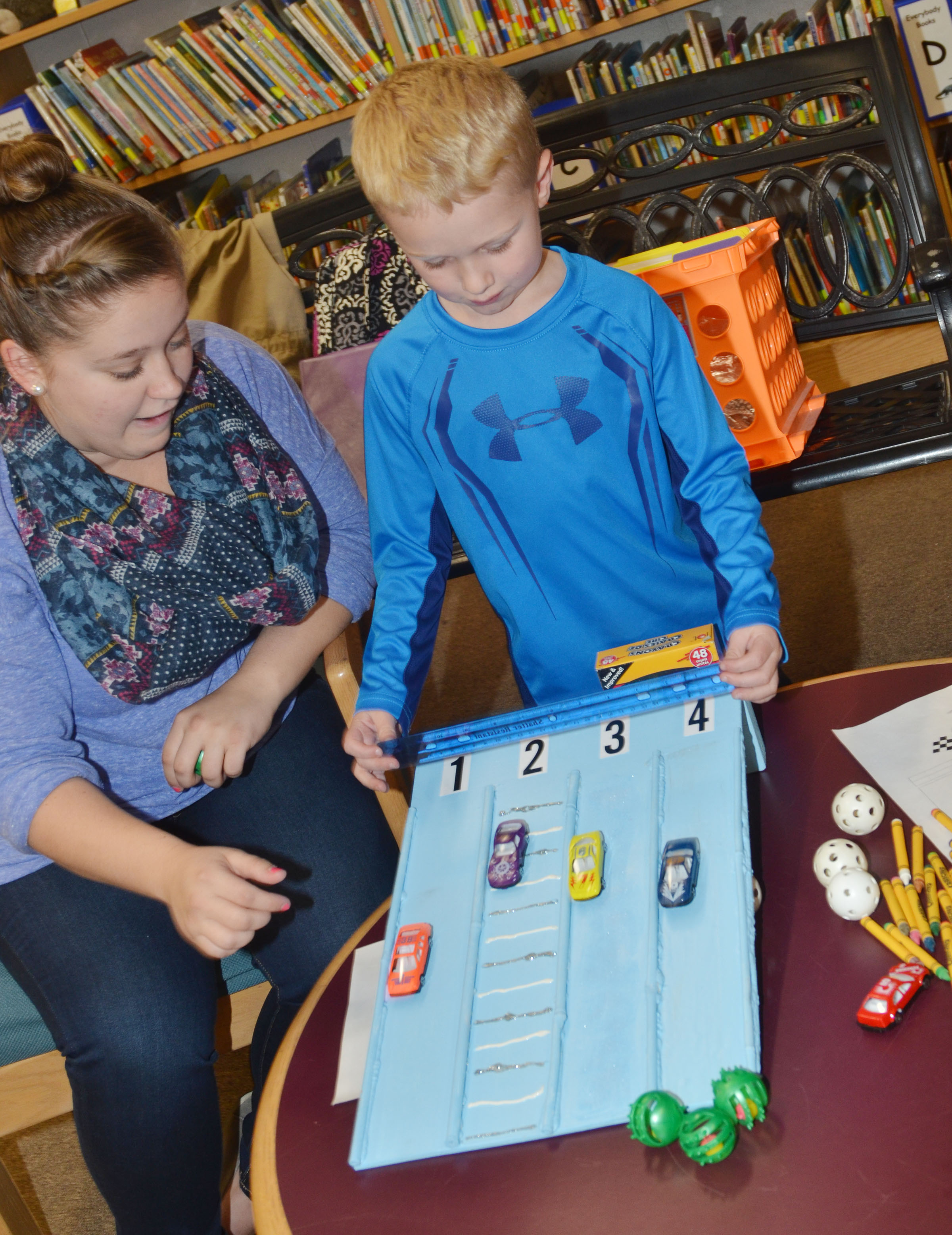 CU early childhood education student Jordyn Bray helps CES kindergartener Jackson Wright determine which type of surface will make a car travel the fastest.