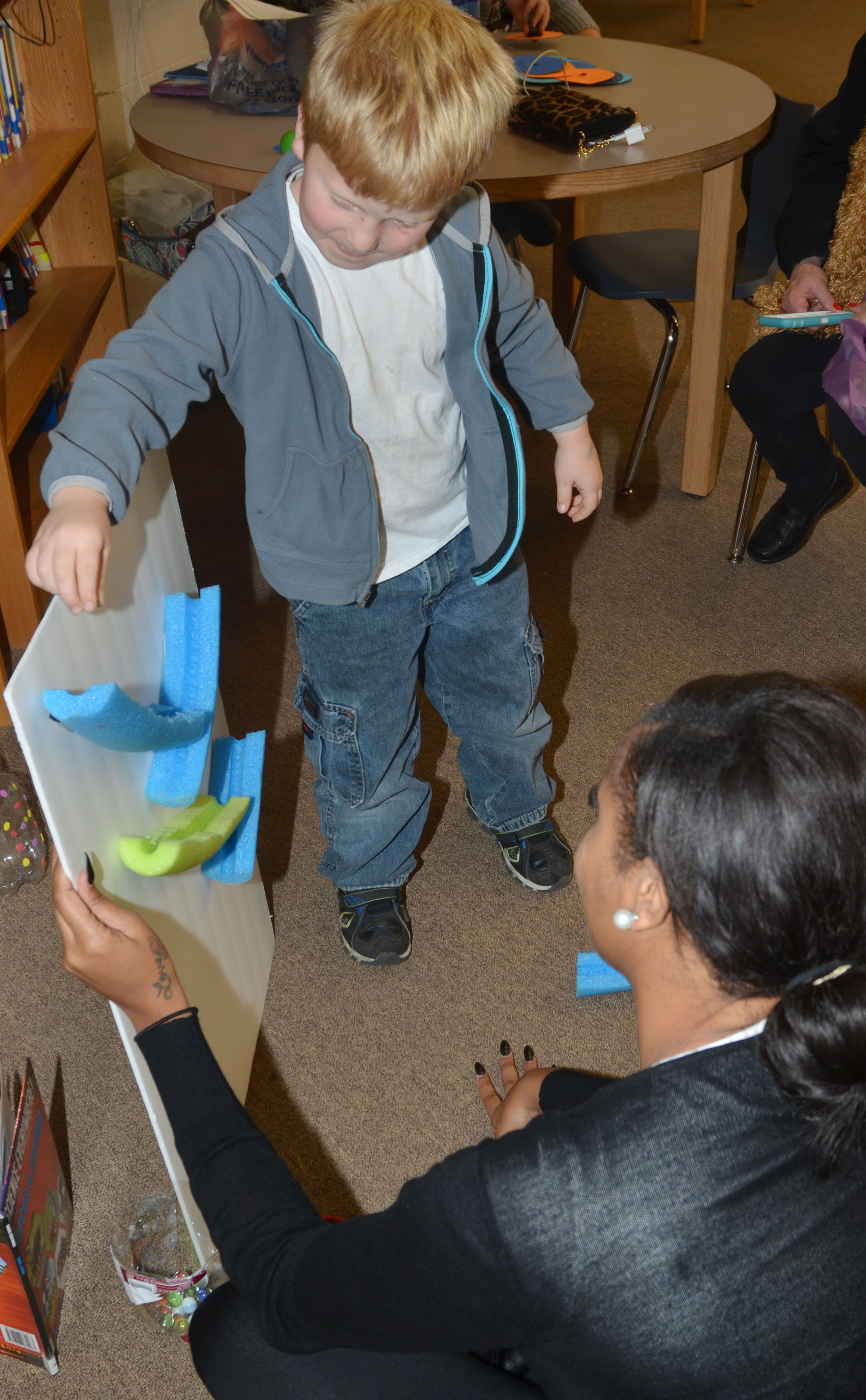 CES first-grader Ben Parrott makes a marble run with CU early childhood education student Dana Phillips.