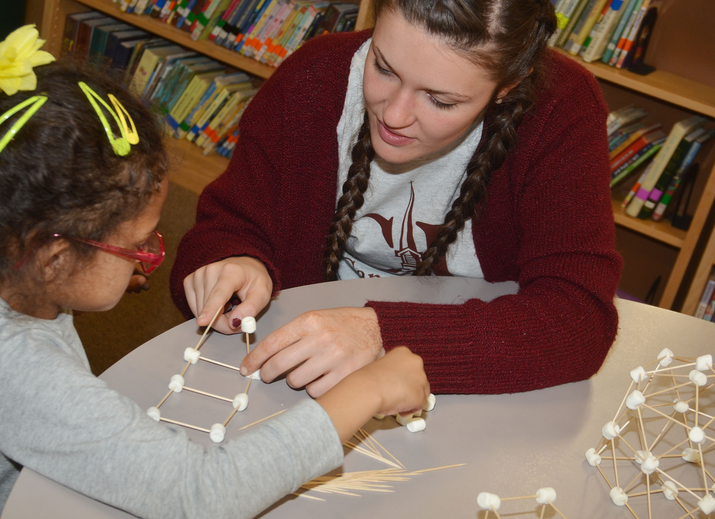 CES kindergartener Marlee Dickens builds a house out of marshmallows and toothpicks with CU early childhood education student Joelle Collett.