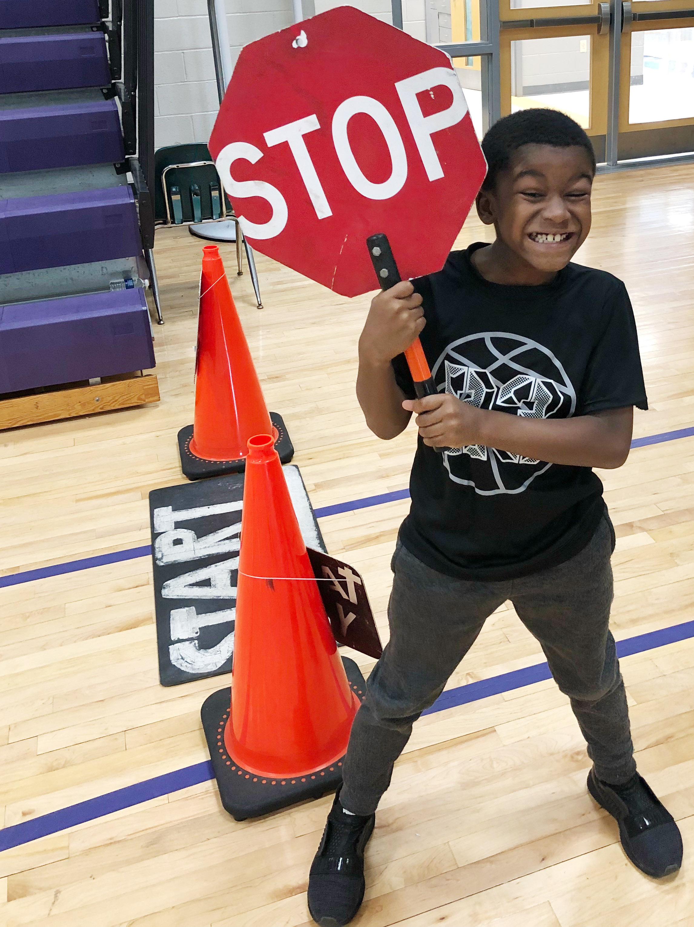 CES fourth-grader Kae'vin Spaulding holds the stop sign as his classmates practice riding their bicycles.