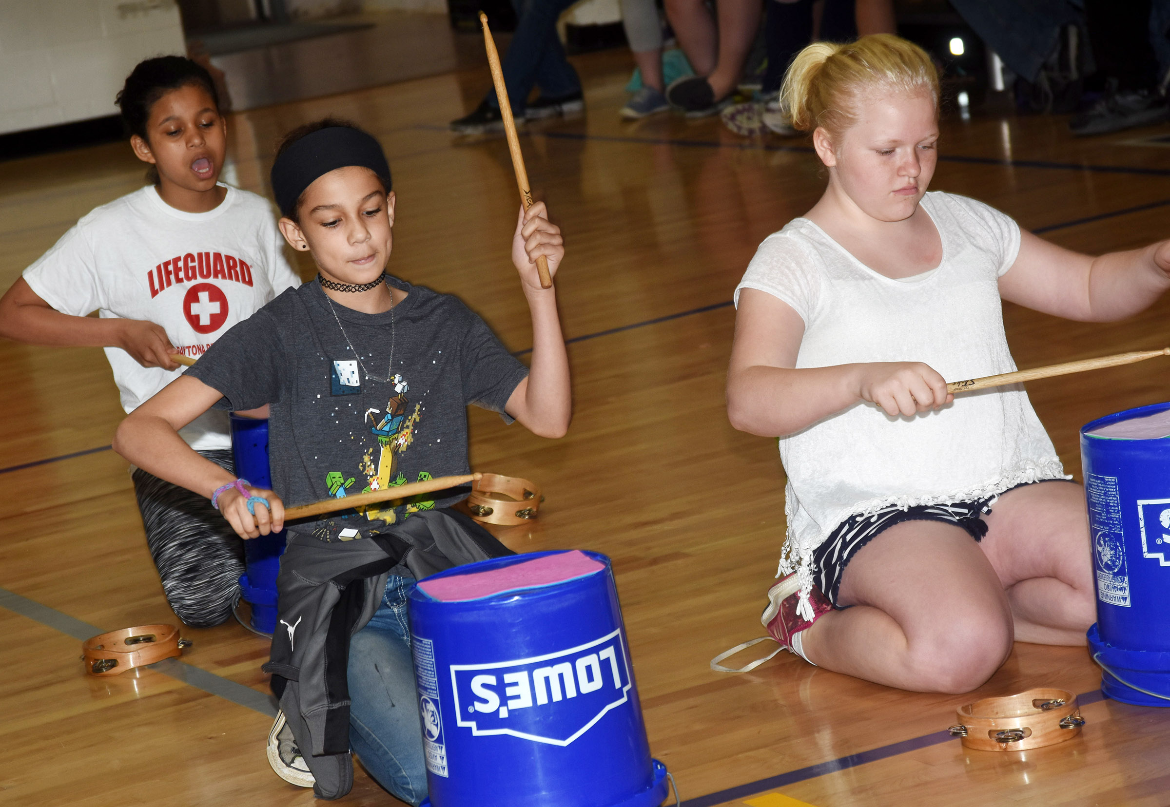CES fifth-graders, from left, Destiny Bradley, Mackenzie Negron and Daisy Wilkerson play the bucket drums.