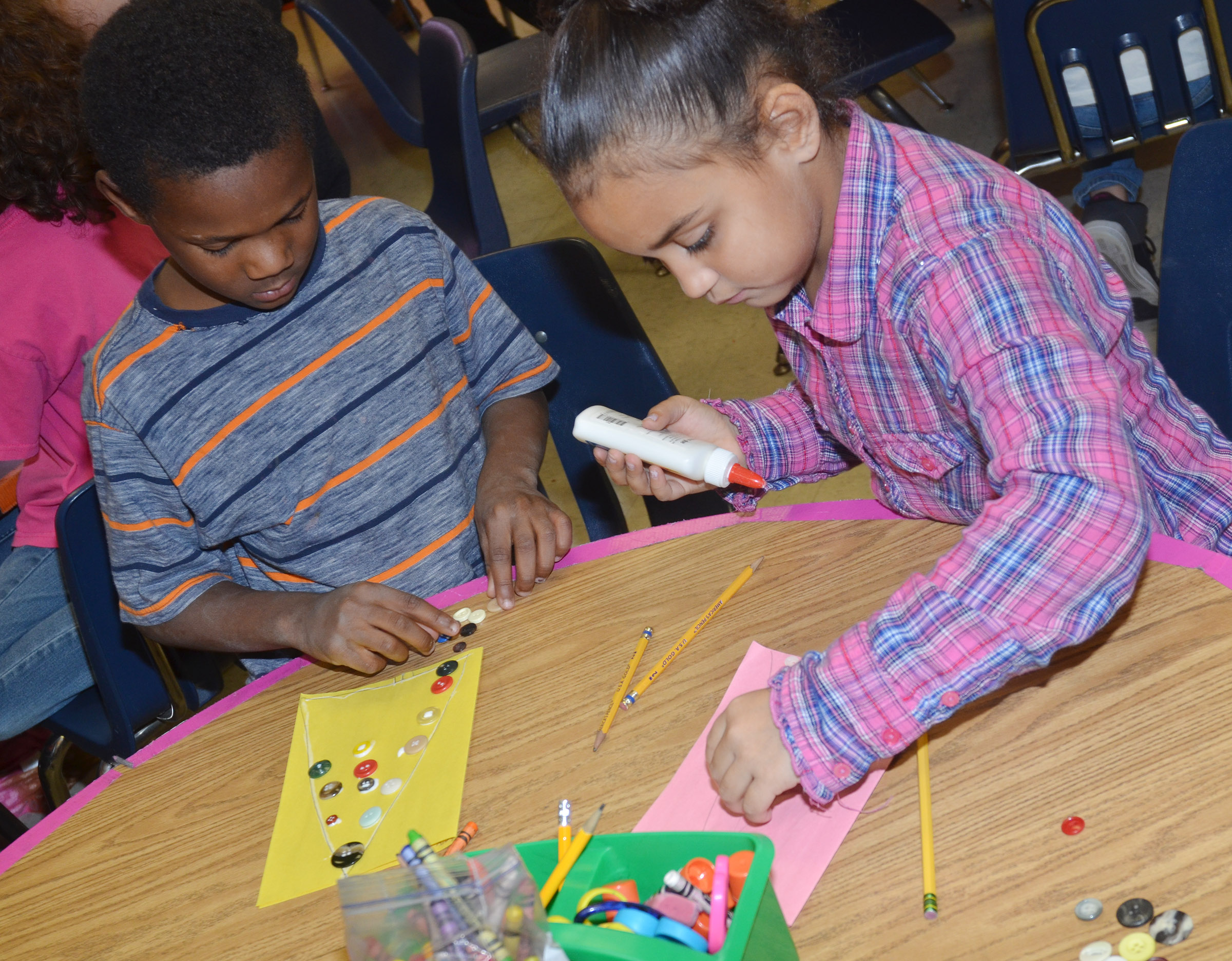 CES first-graders Lazarick Miller, at left, and Maleigha Travis glue buttons on their trees.
