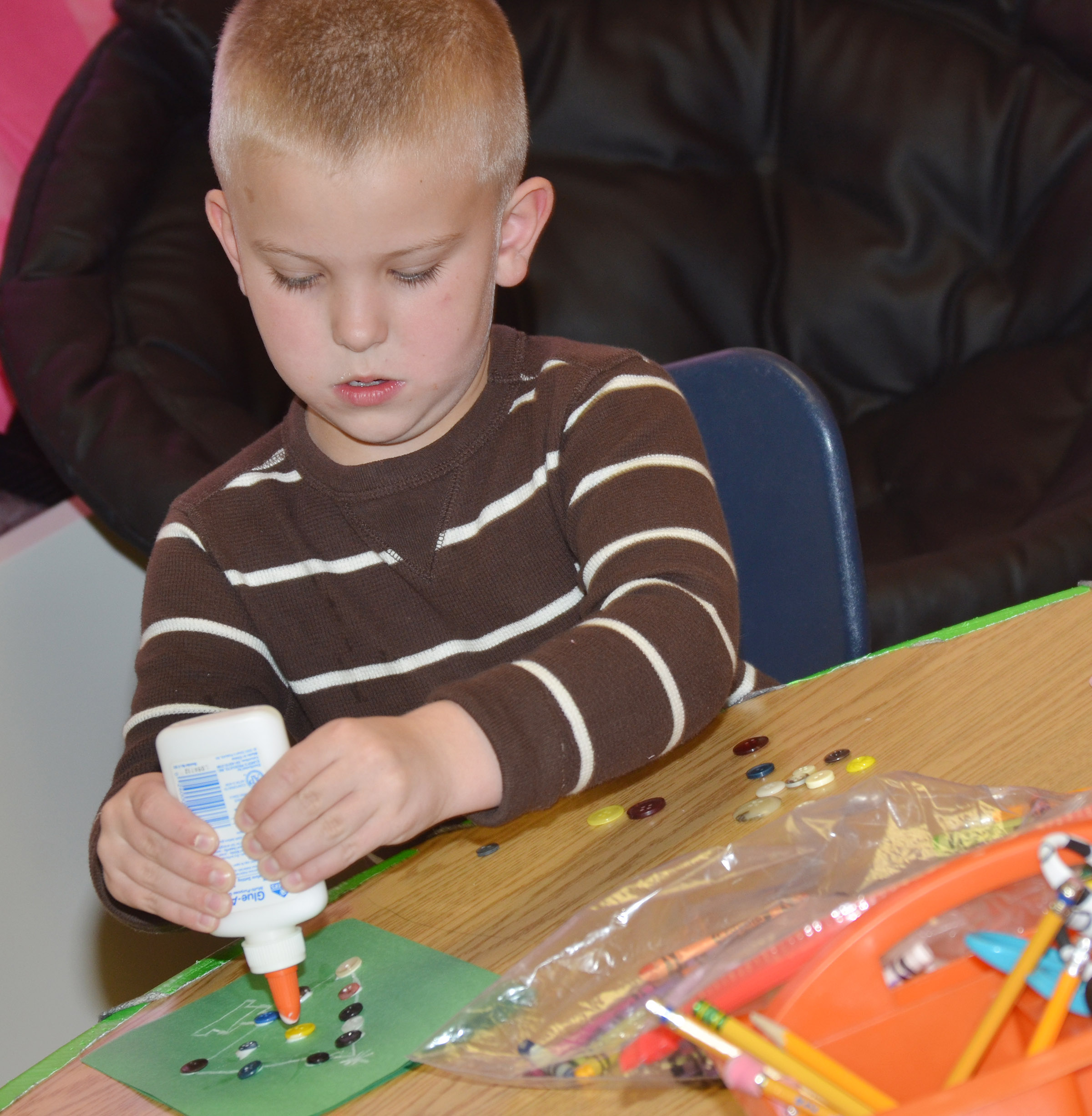 CES first-grader Ethan Bailey glues buttons on his trees.