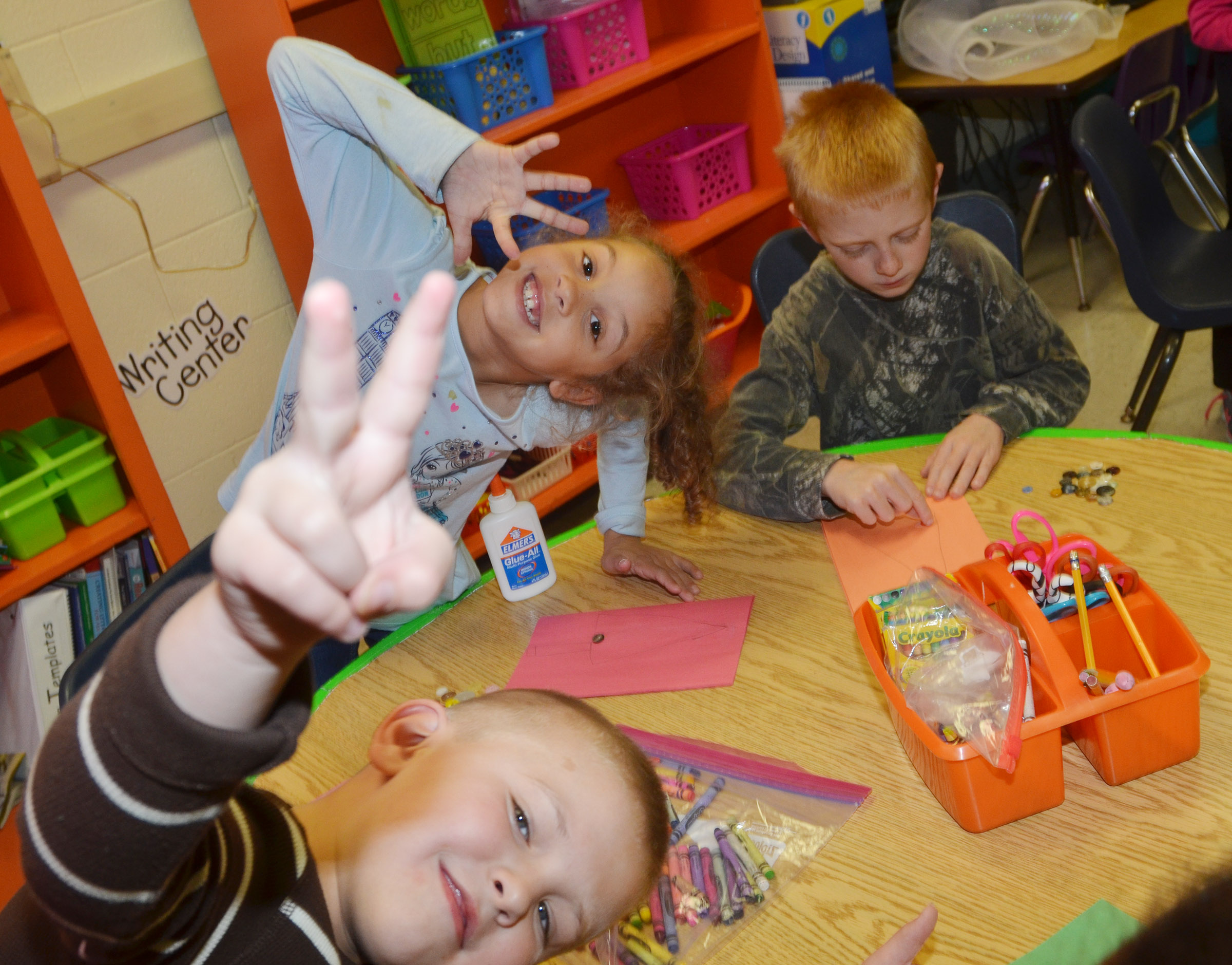 CES first-graders Brady Cox and Keiava Thompson smile for the camera as Jacob Wethington works on his tree.