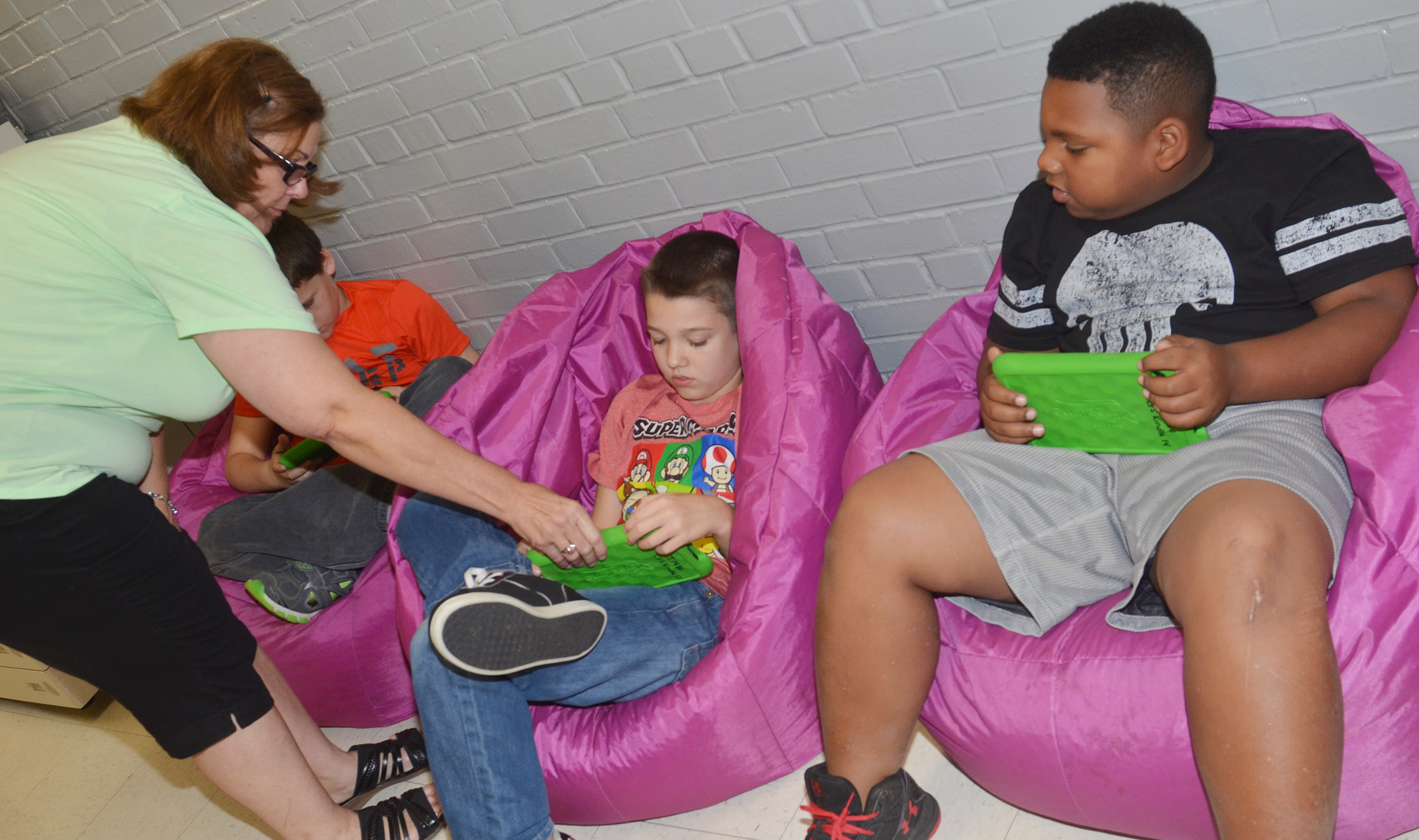 CES exceptional child educator Libby Caulk helps fourth-graders Landon Tucker, at left, and Malikiah Spurling work math problems on their Kindles via the Star Math program.