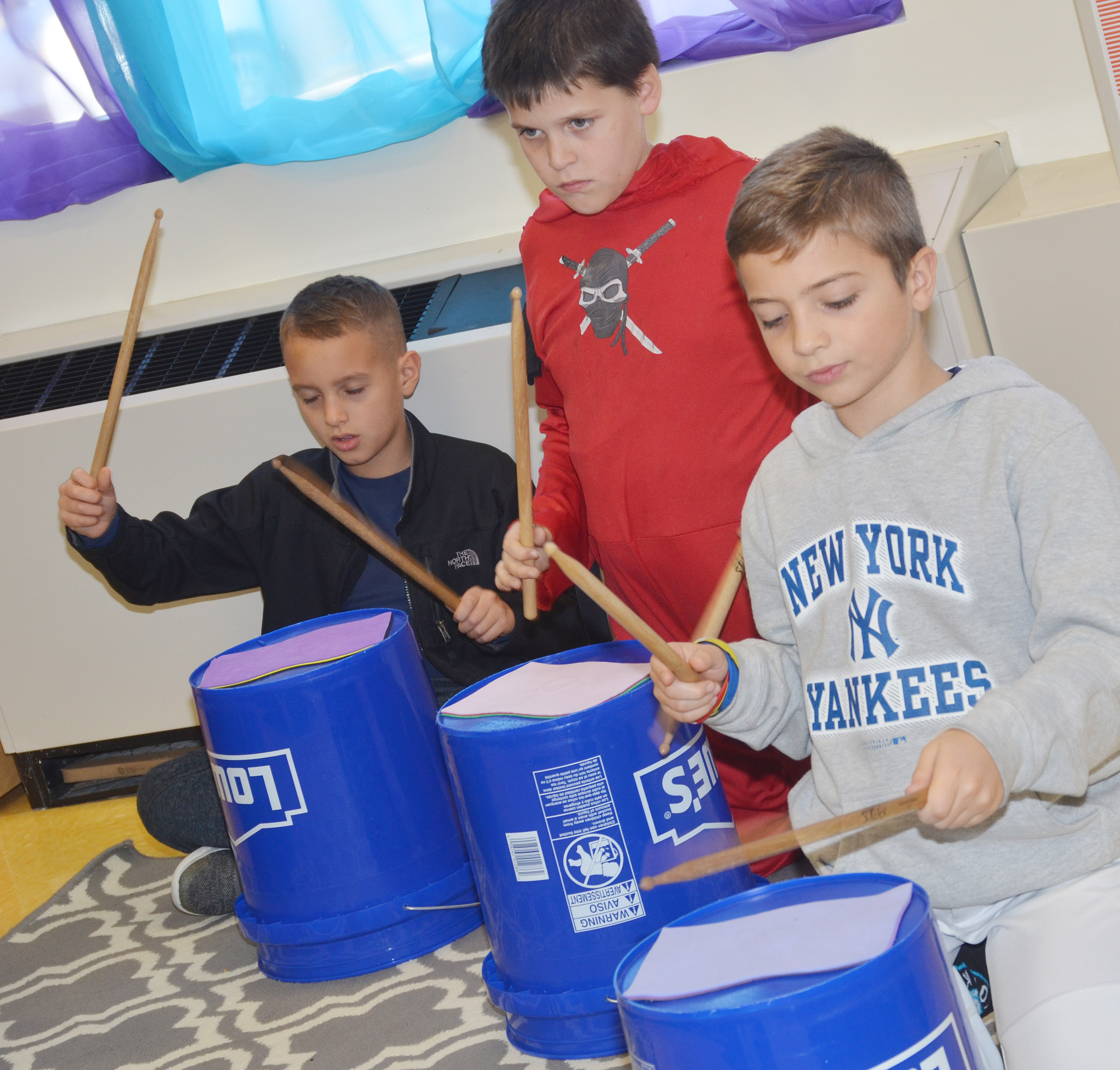 CES fourth-graders, from left, Bradley Paris, Chris Brown and Carson Mills play the bucket drums.