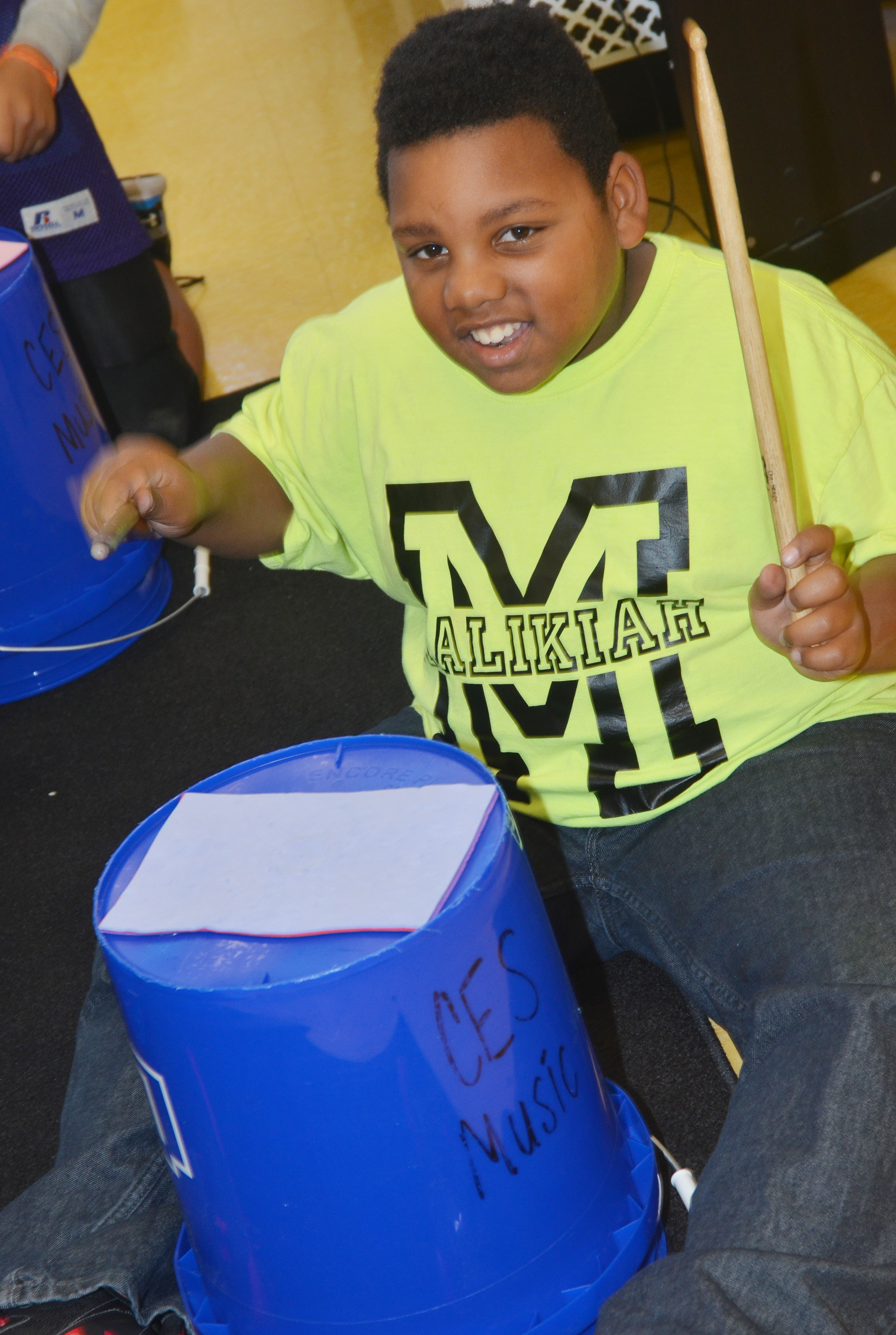 CES fourth-grader Malikiah Spurling plays the bucket drums.