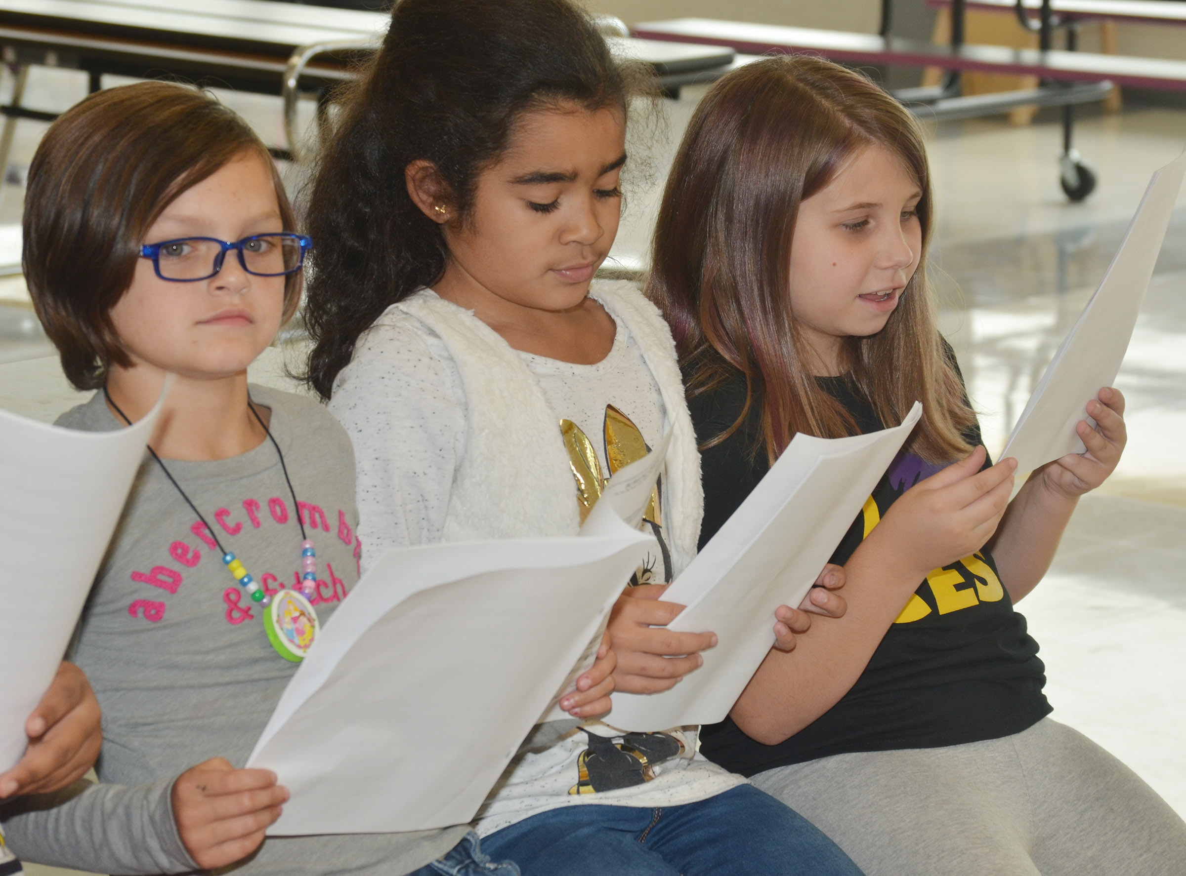 From left, CES third-graders KayLee Lamer, Sophia Santos and Natalia West sing.
