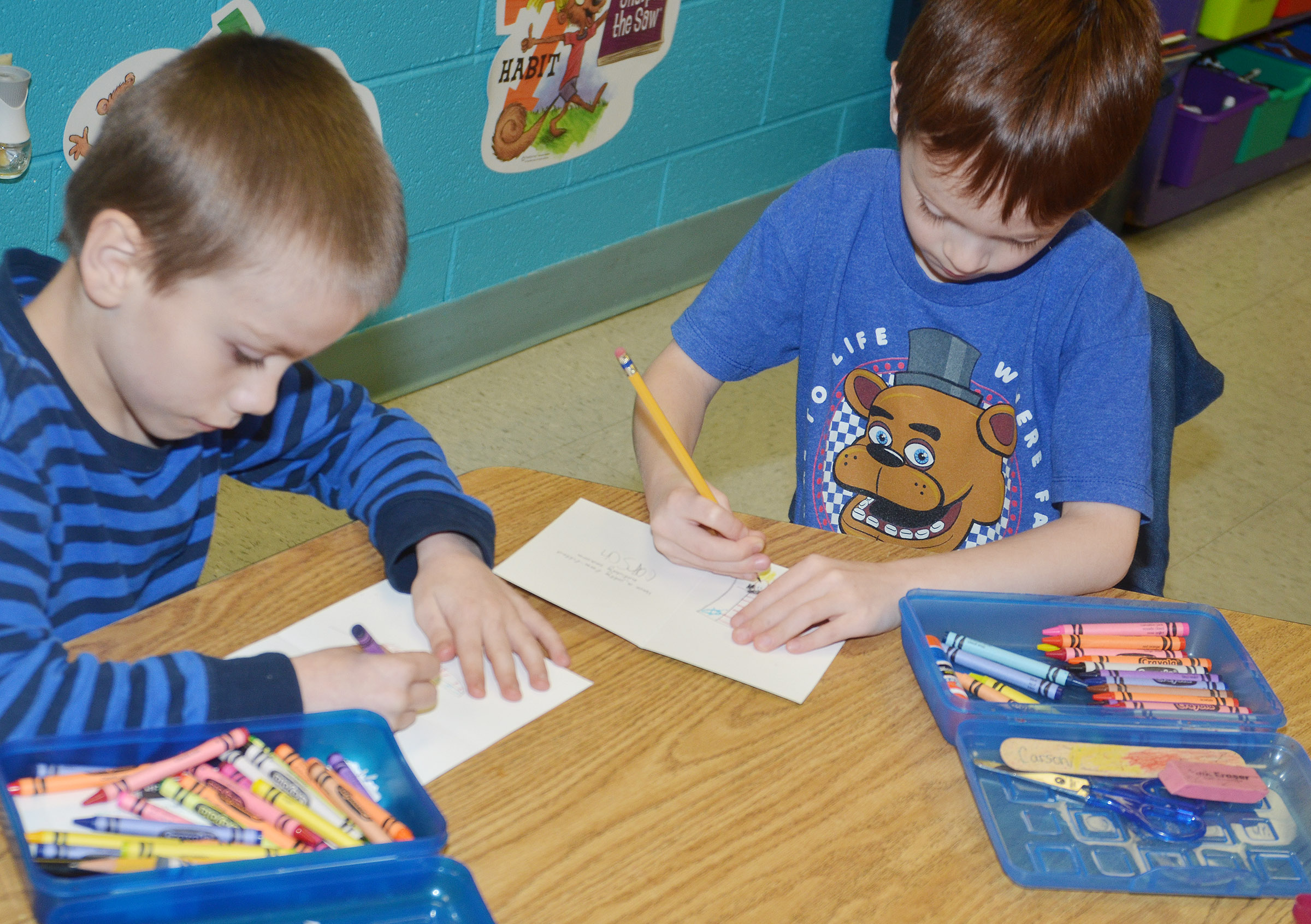 CES first-graders Alex Eggers, at left, and Carson Montes make Christmas cards for soldiers.