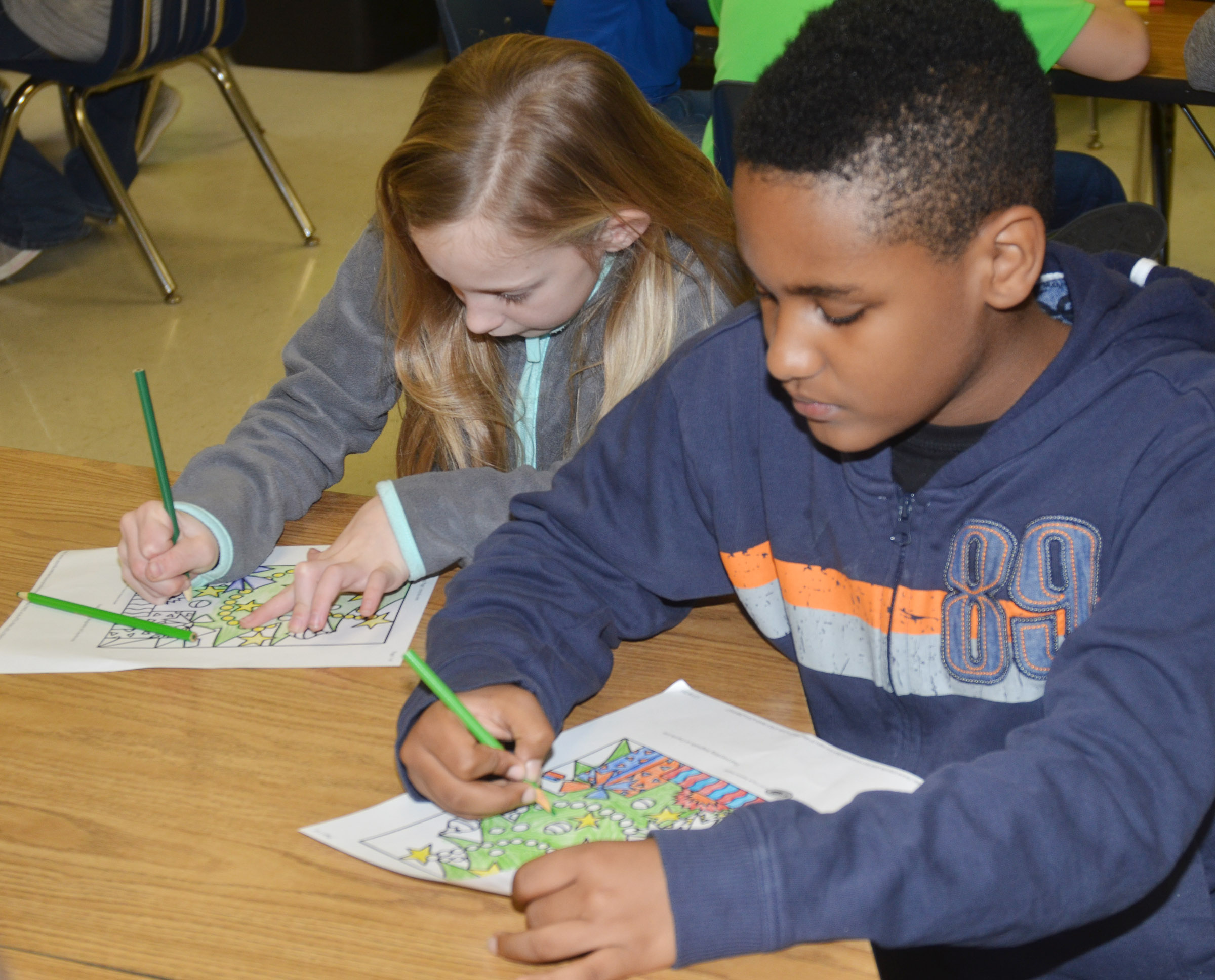 CES fourth-graders Kendall Bright, at left, and Shaiden Calhoun enjoy coloring a Christmas scene.