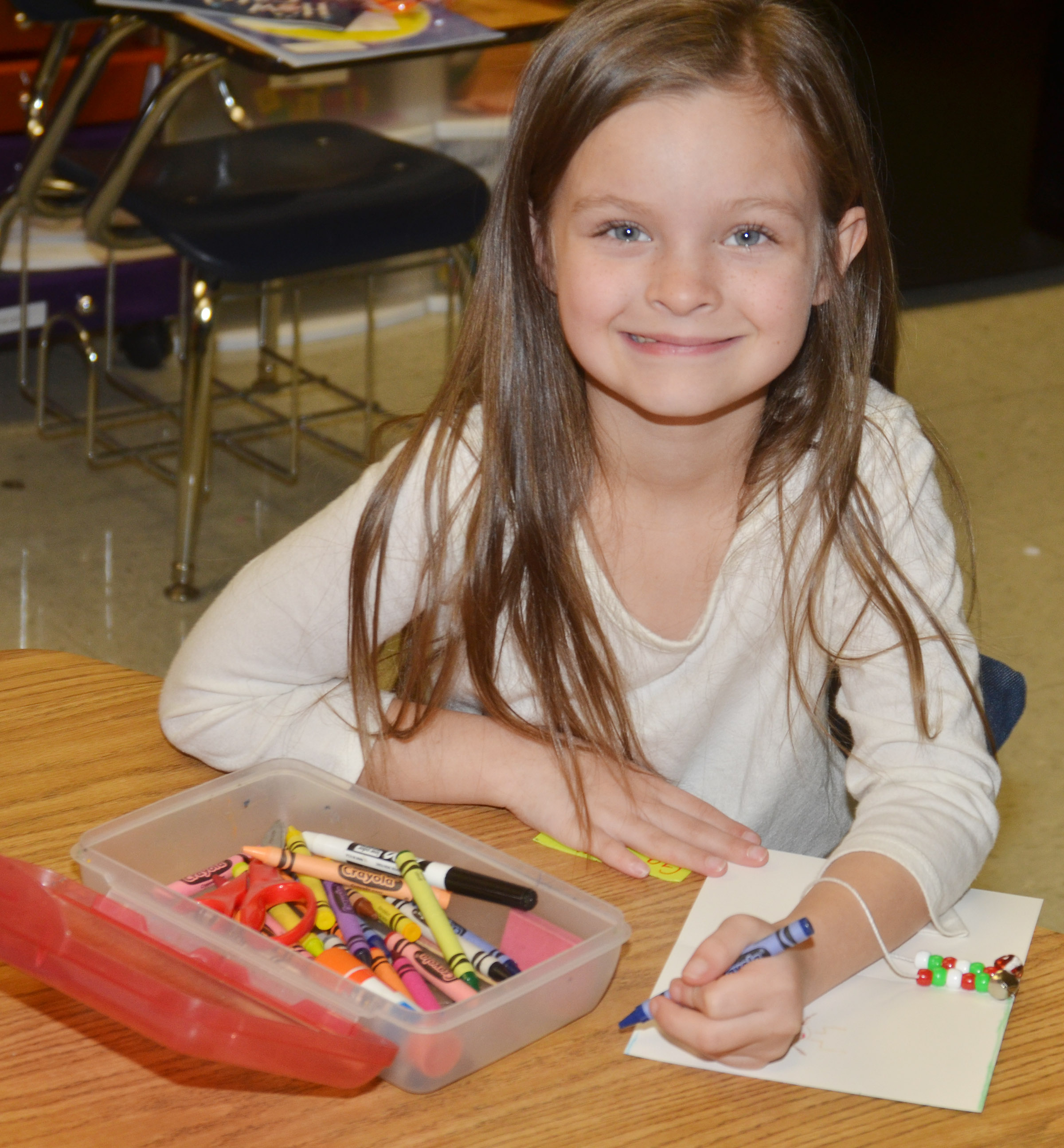 CES first-grader Addison Perkins smiles as she makes a Christmas card for a soldier.