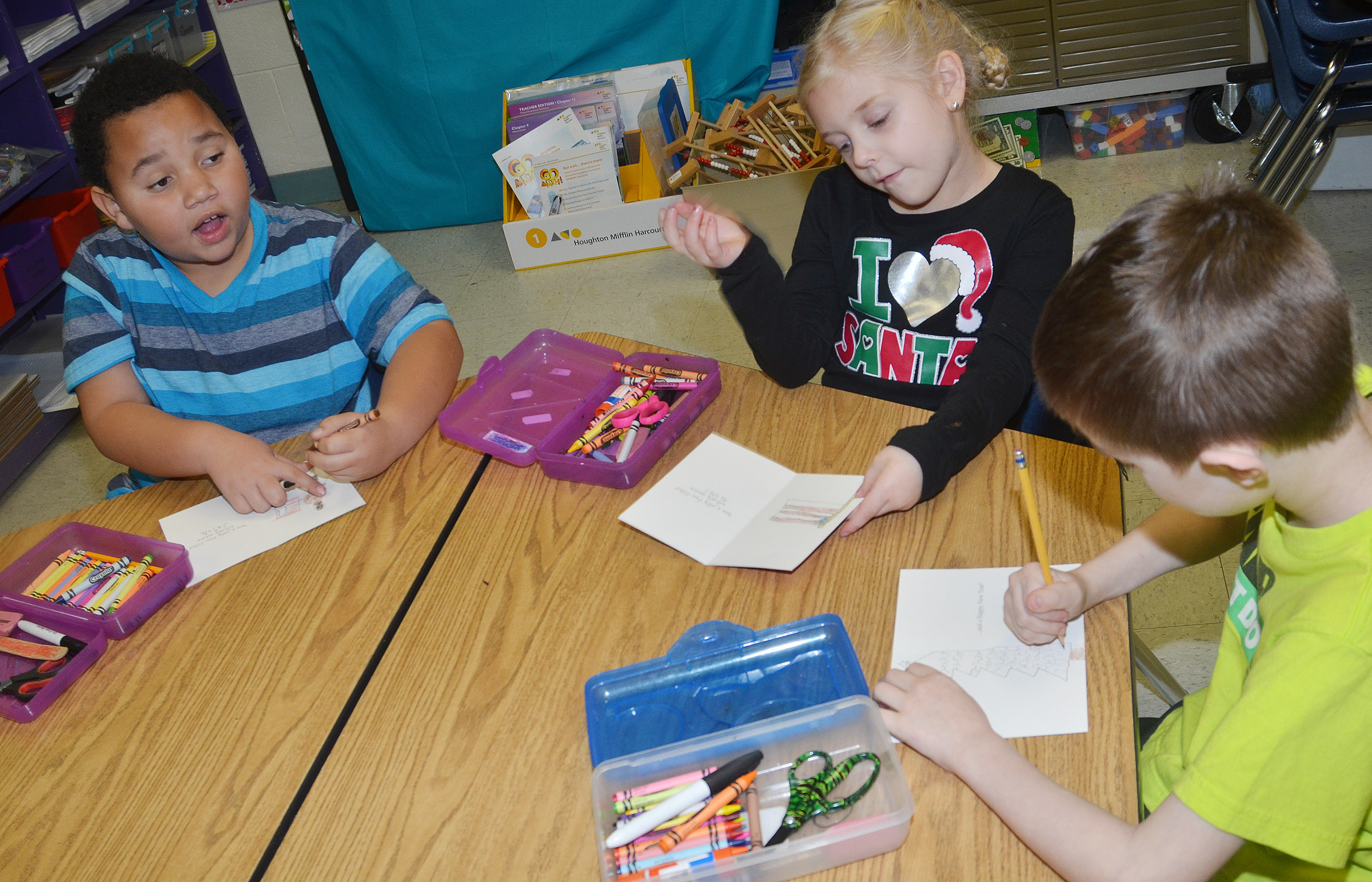 CES first-graders, from left, Justin Walls, Aubrey Novak and Caleb Goodson make Christmas cards for soldiers.