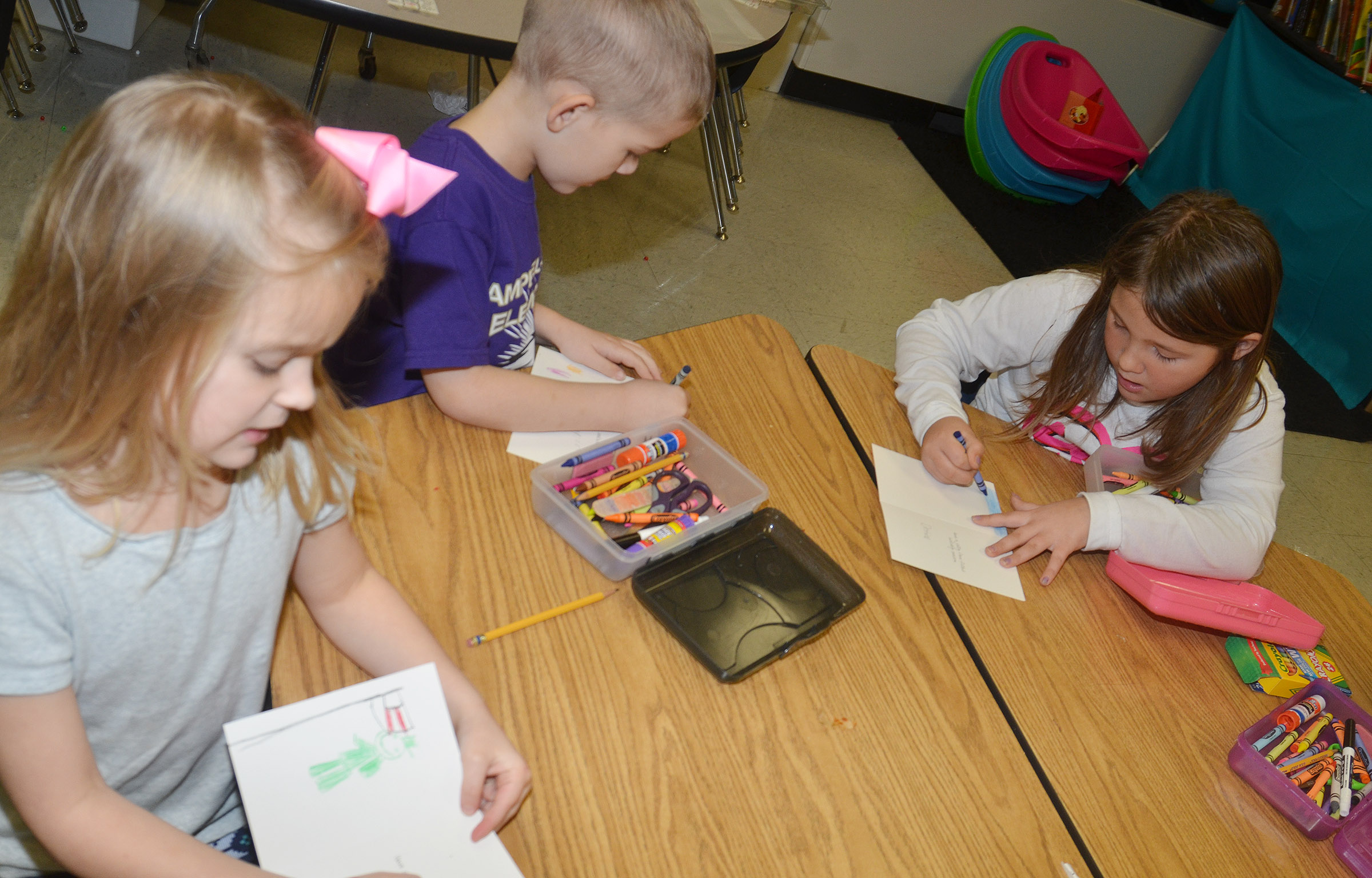 From left, CES first-graders Miley Orberson, Mason Edwards and Destiny Rhinehart make Christmas cards for soldiers.