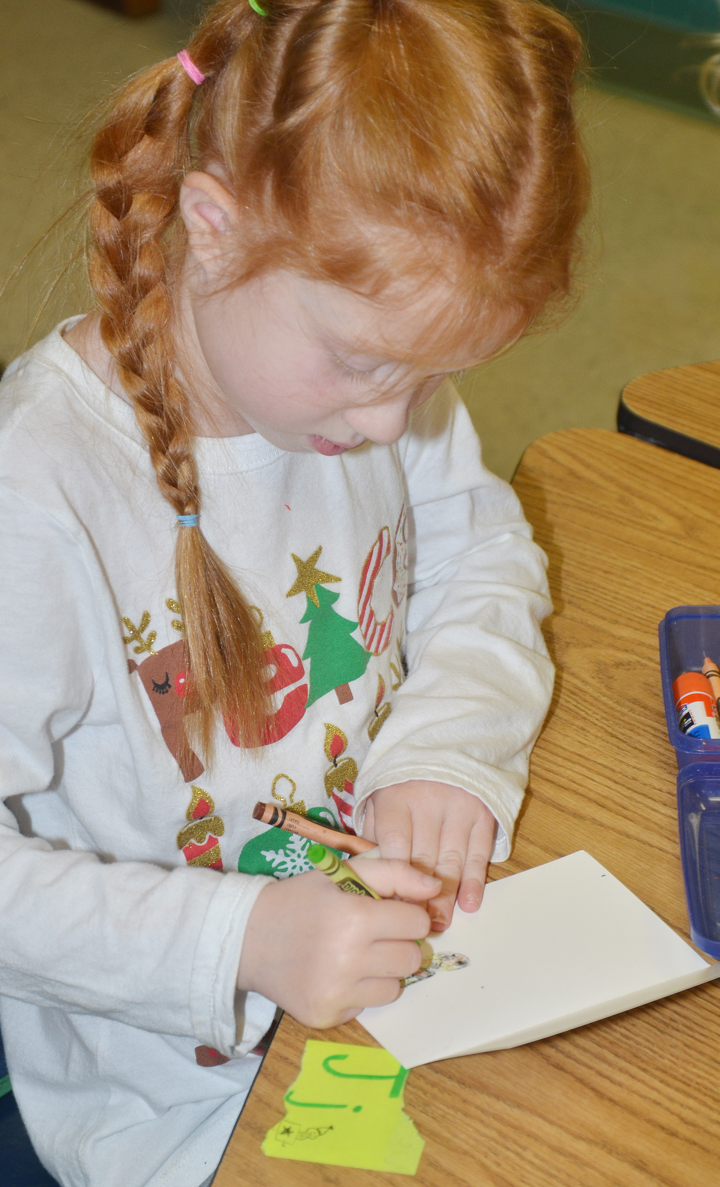 CES first-grader Bella Stout makes a Christmas card for a soldier.