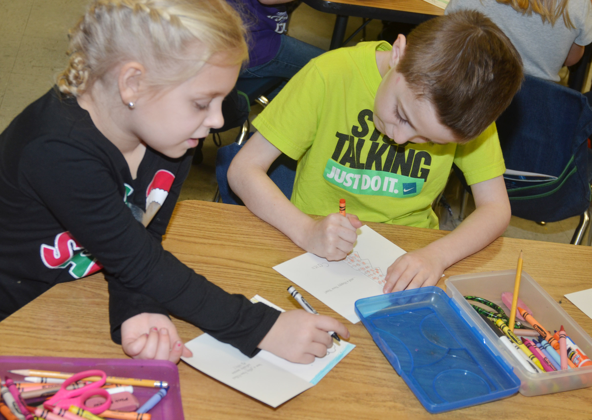 CES first-graders Aubrey Novak, at left, and Caleb Goodson make Christmas cards for soldiers.