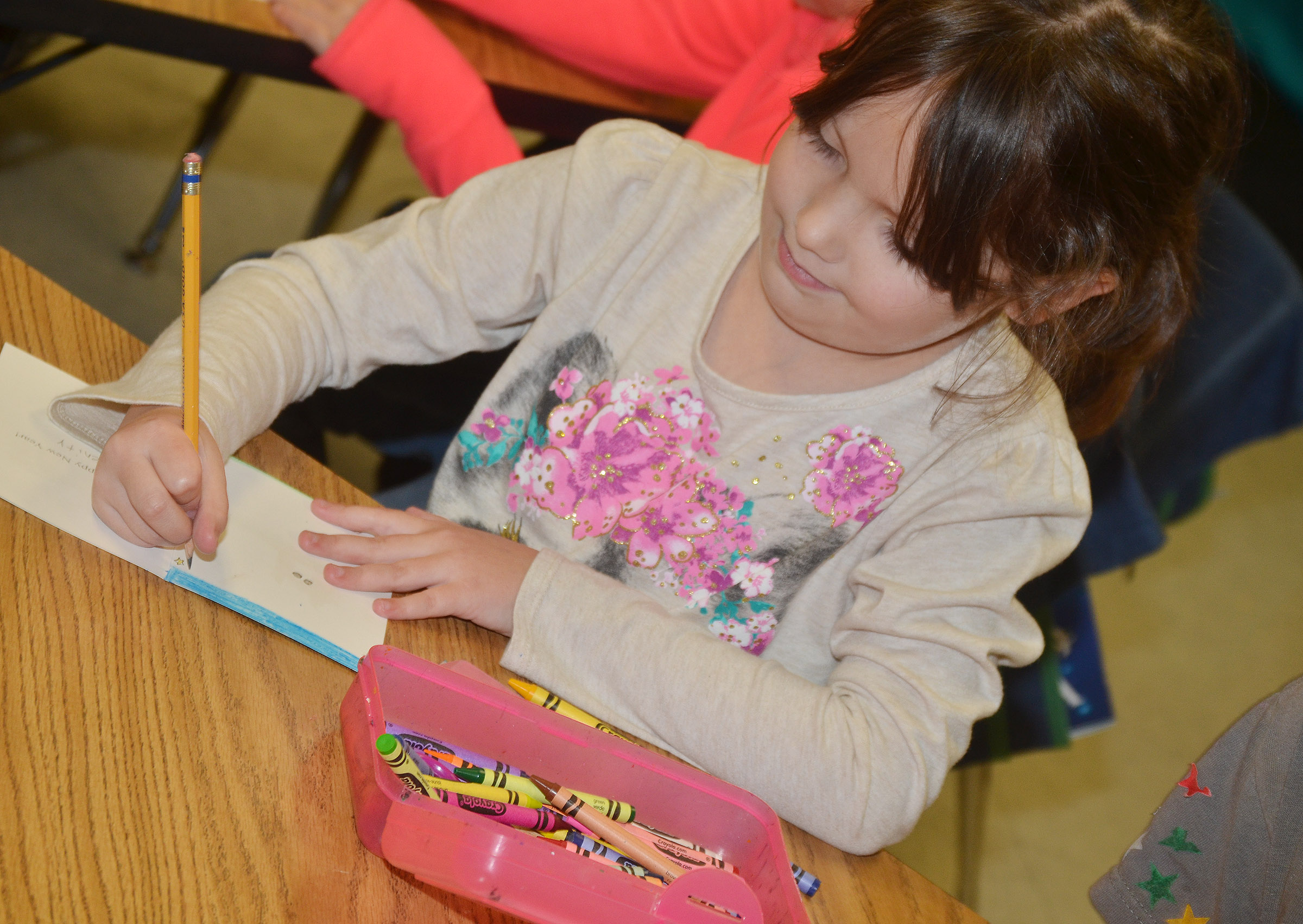 CES first-grader Serenity Brown makes a Christmas card for a soldier.