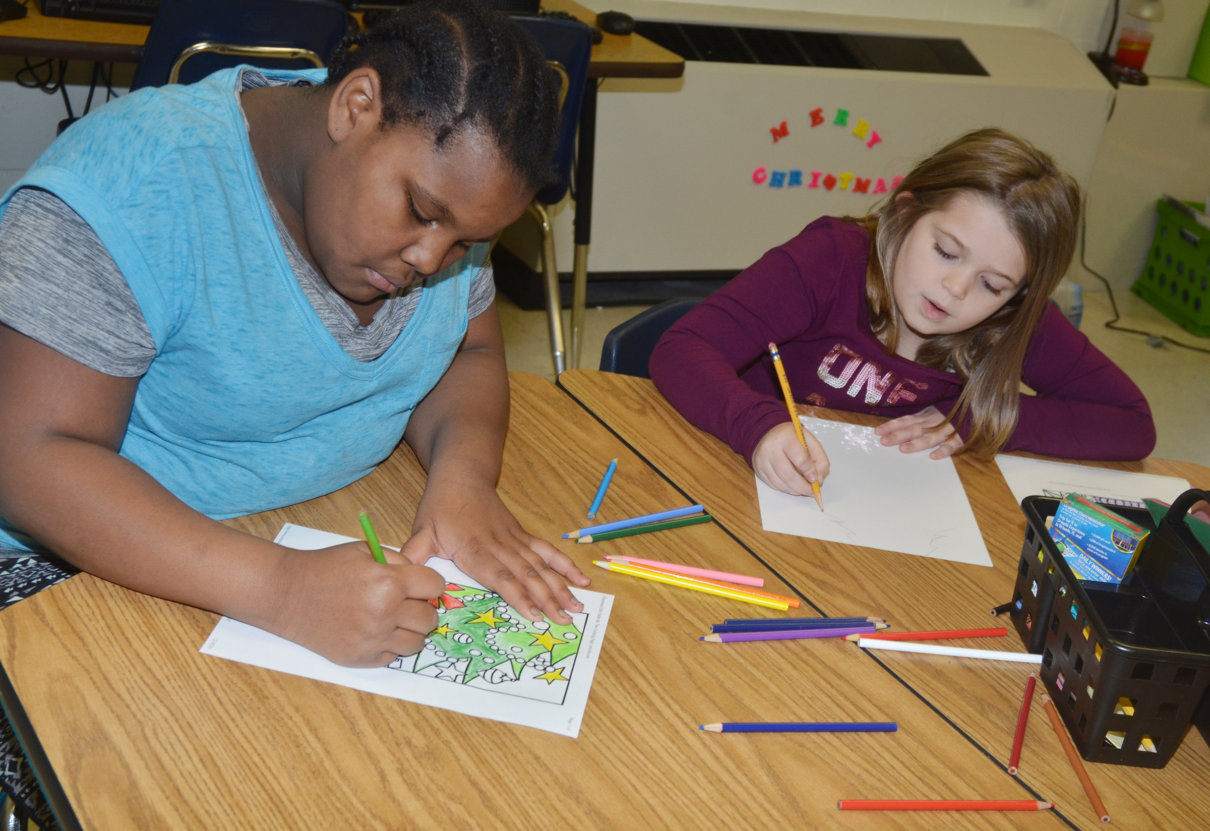 CES fourth-graders Talaysia Daniels, at left, and Chyanne Christie enjoy coloring a Christmas scene.