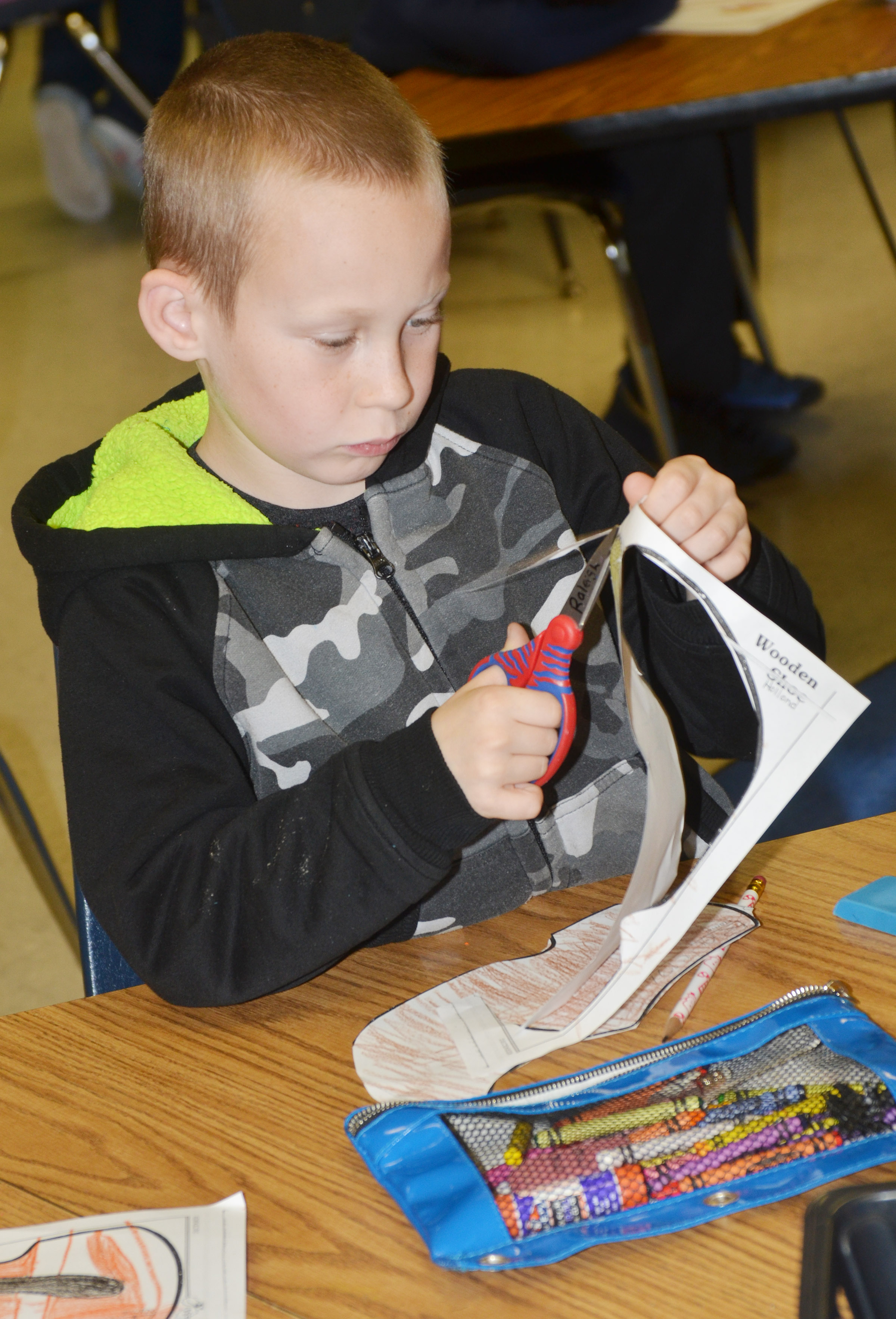 CES second-grader Raleigh Spencer cuts out his wooden shoe after learning about the holiday traditions in the Netherlands.