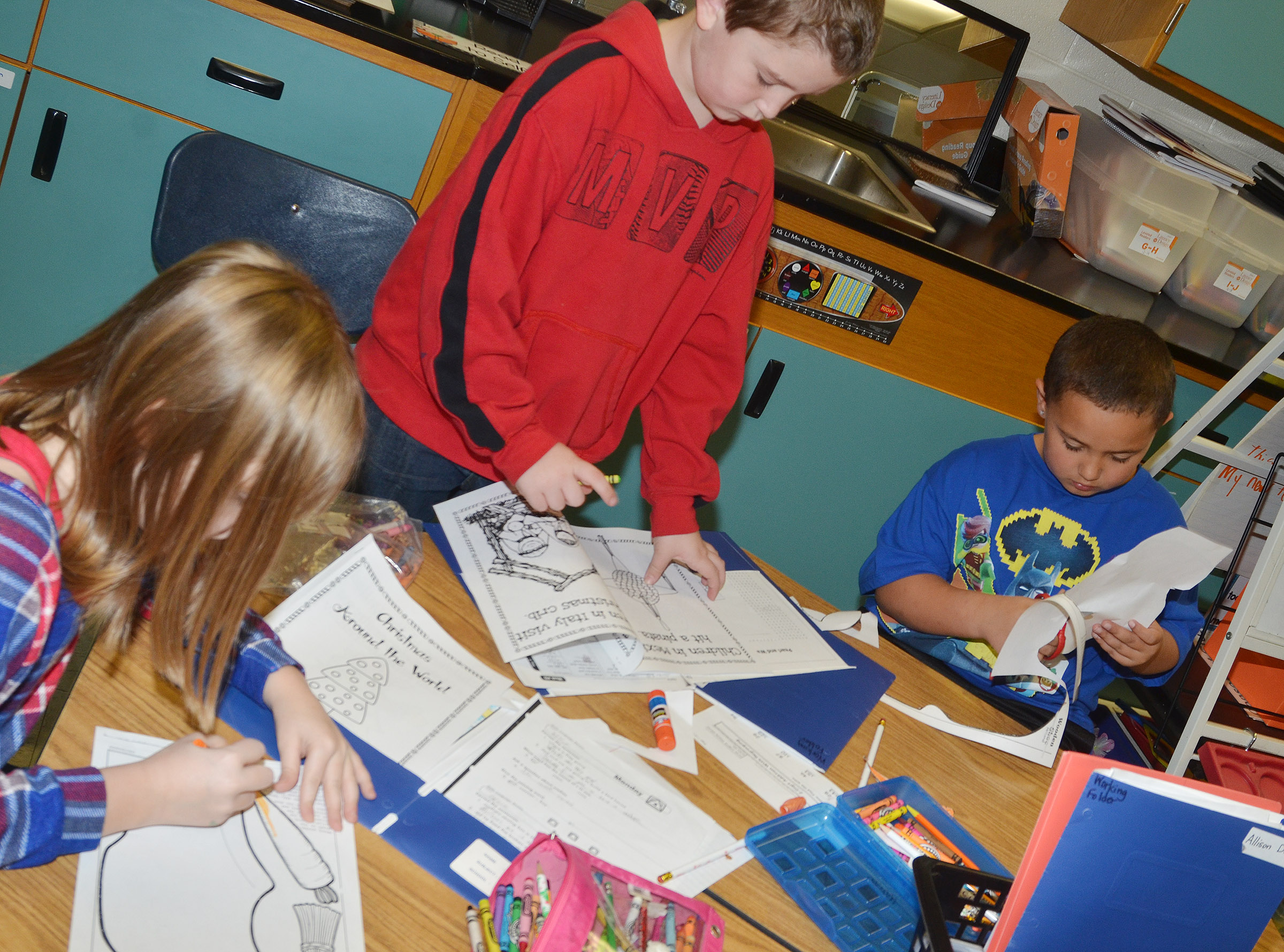 From left, CES second-graders Gracie Murphy, Kevin Bradfield and Marion Mann color their worksheets after learning about the holiday traditions in the Netherlands.