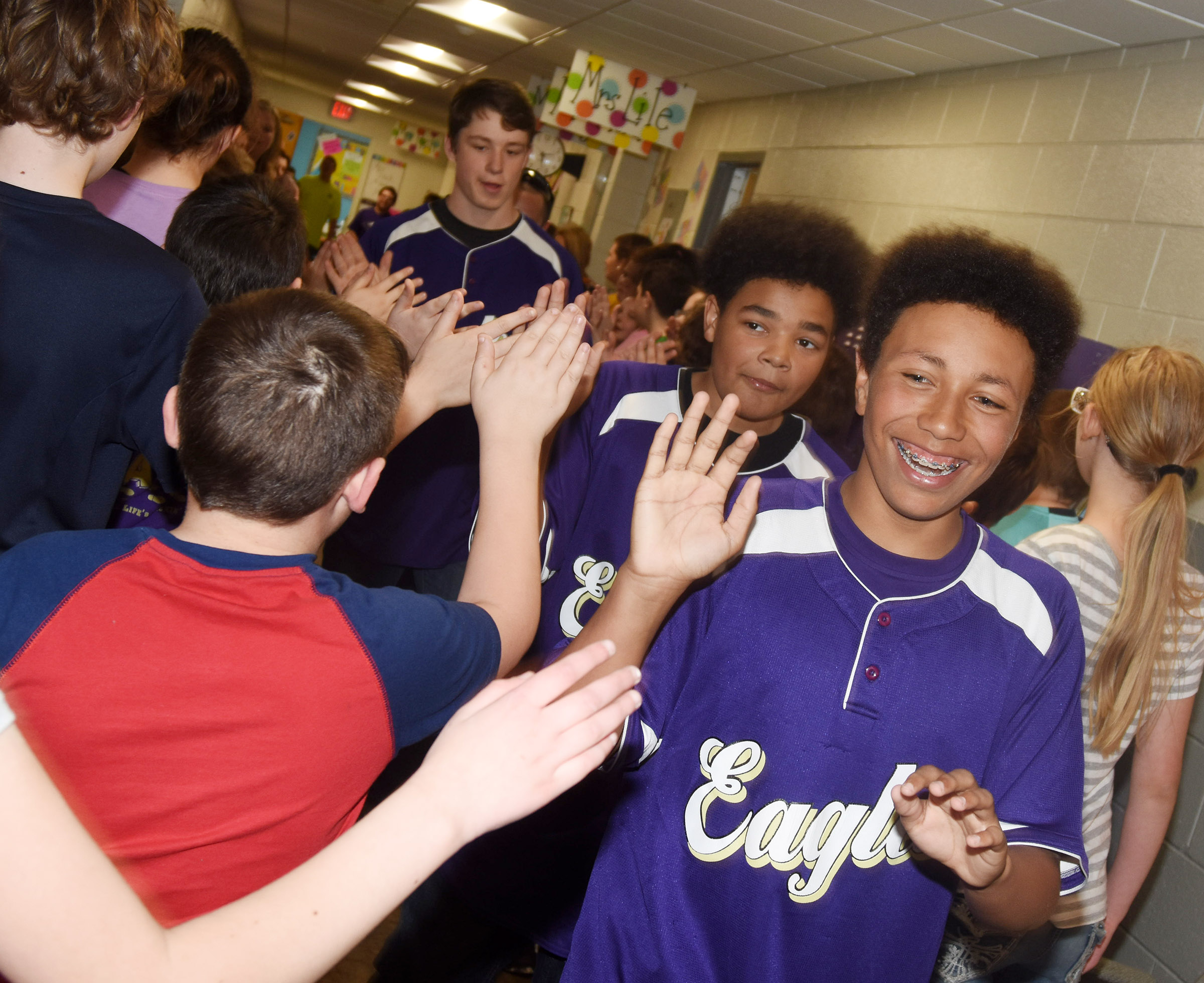 CHS freshman Jastyn Shively and his teammates high-five CES students.