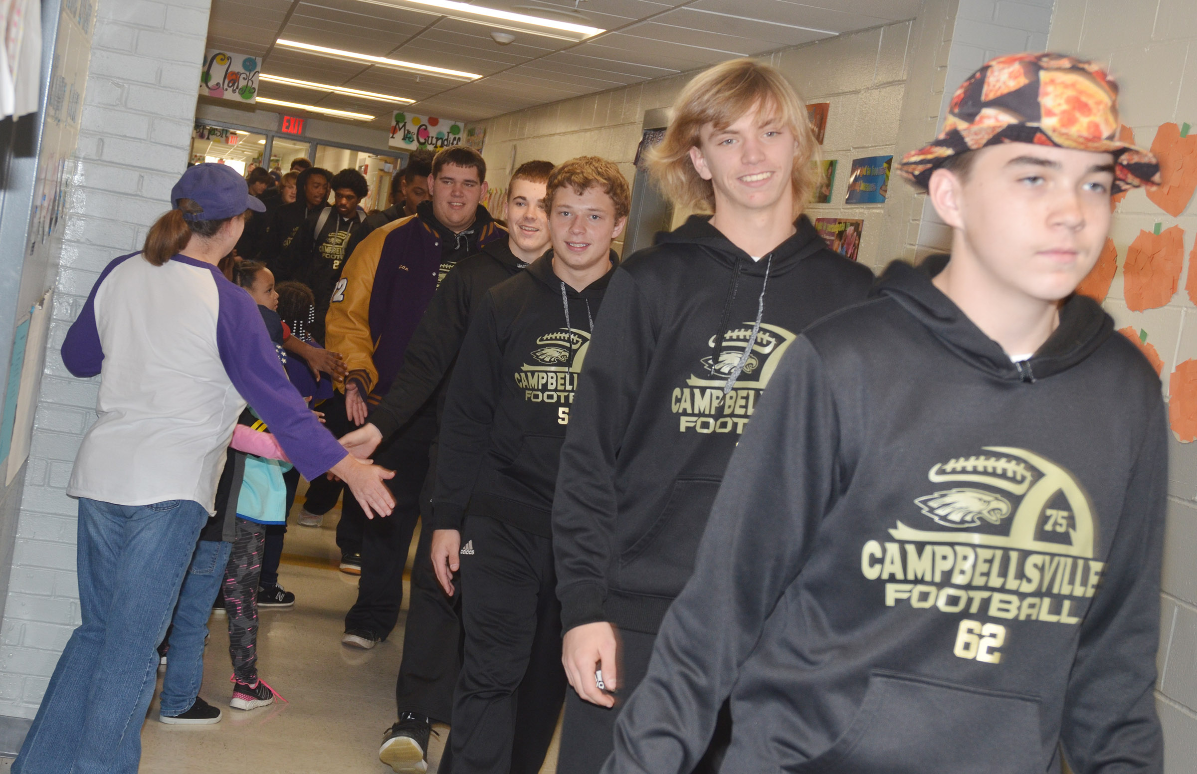 CHS football players walk down the CES hallway.