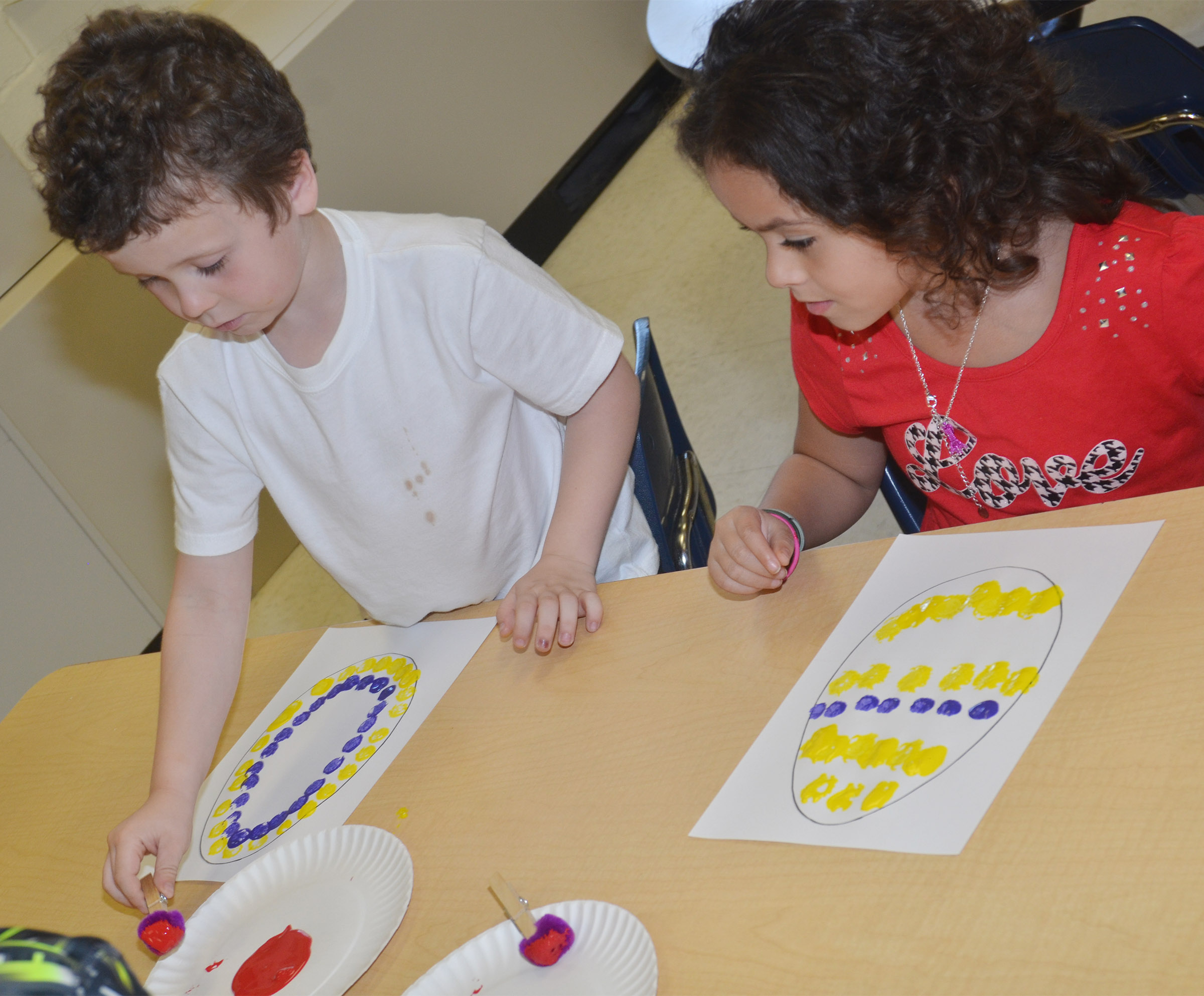 CES kindergarteners Braydan Dyer, at left, and Isabella Anderson paint their Easter eggs.