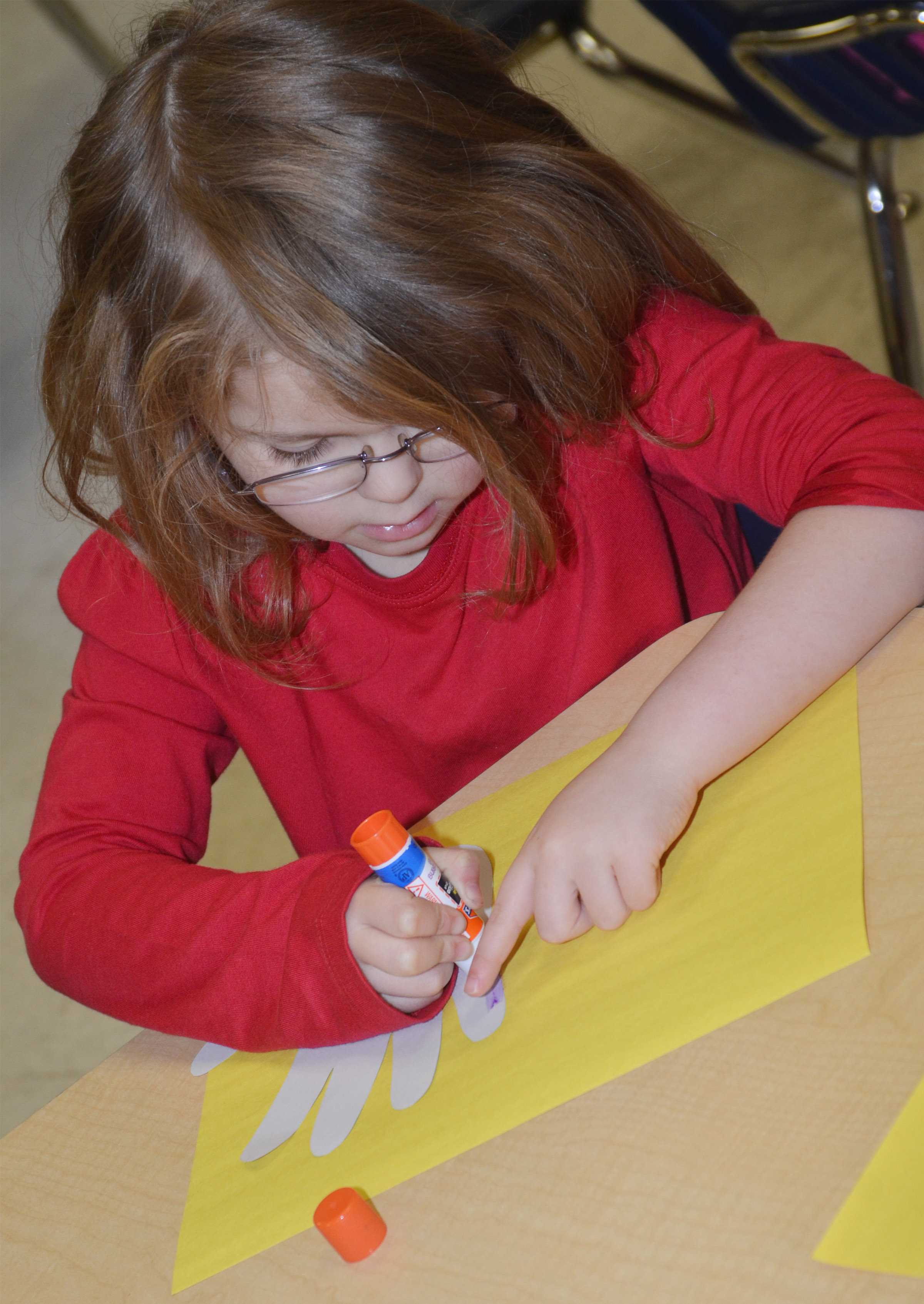 CES kindergartener Aubrey Wilson glues her hand, which will become Horton's face, to her construction paper.