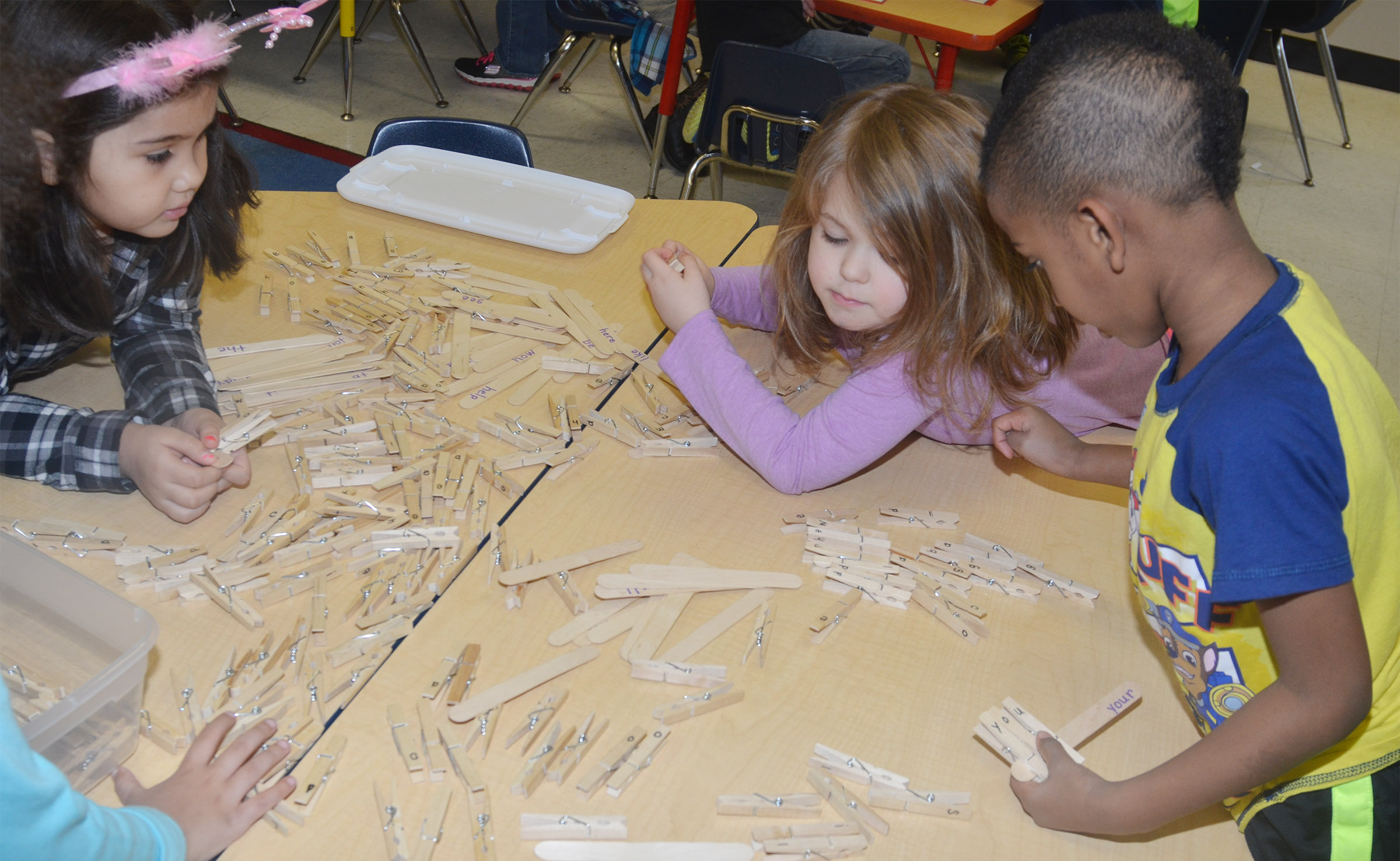 From left, CES kindergarteners Hannah Matias, Aubrey Wilson and Kasen Smith search for letters as they spell words with clothes pins.