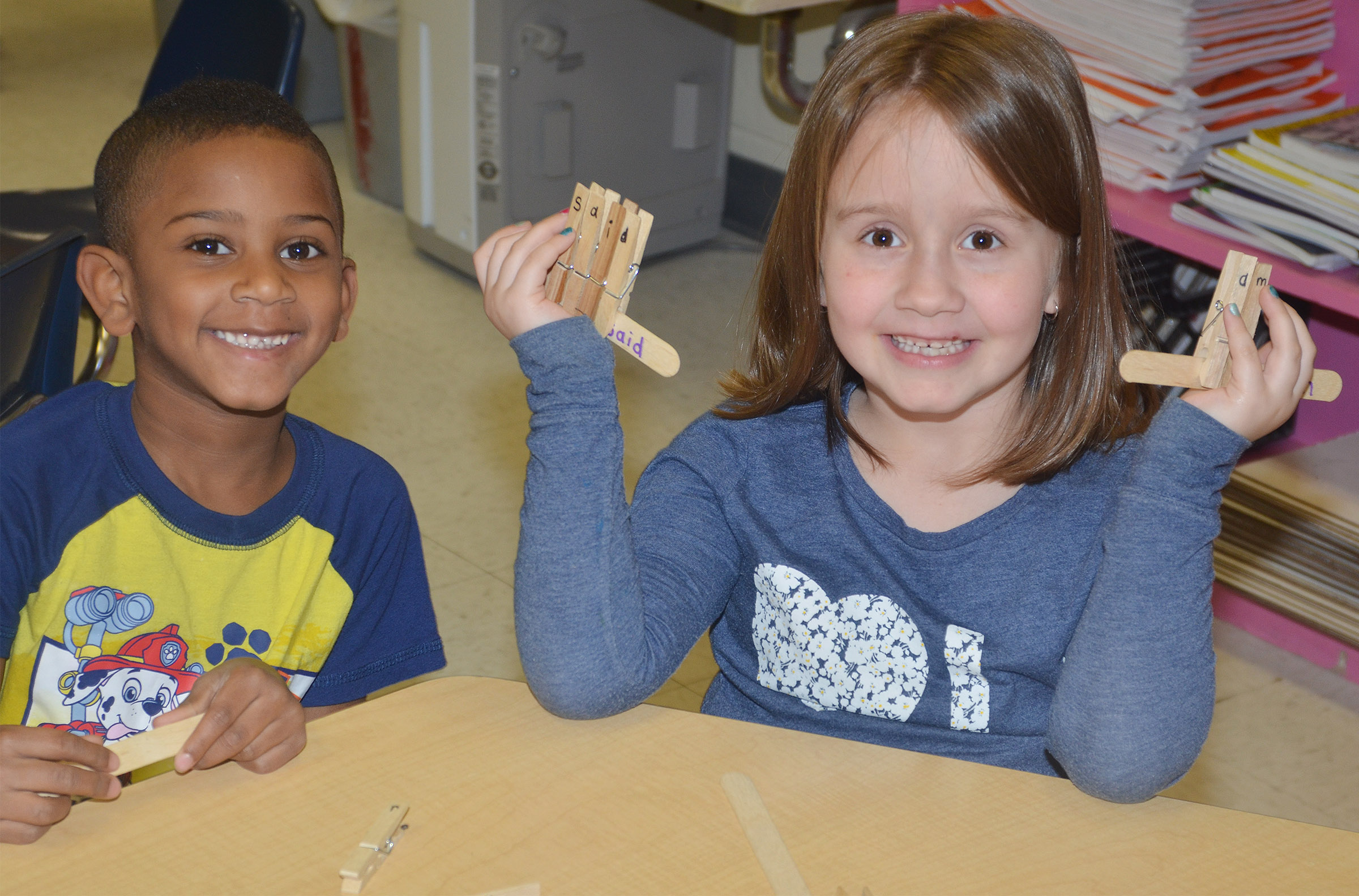 CES kindergarteners Kasen Smith, at left, and Natalee Shaw spell words with clothes pins.