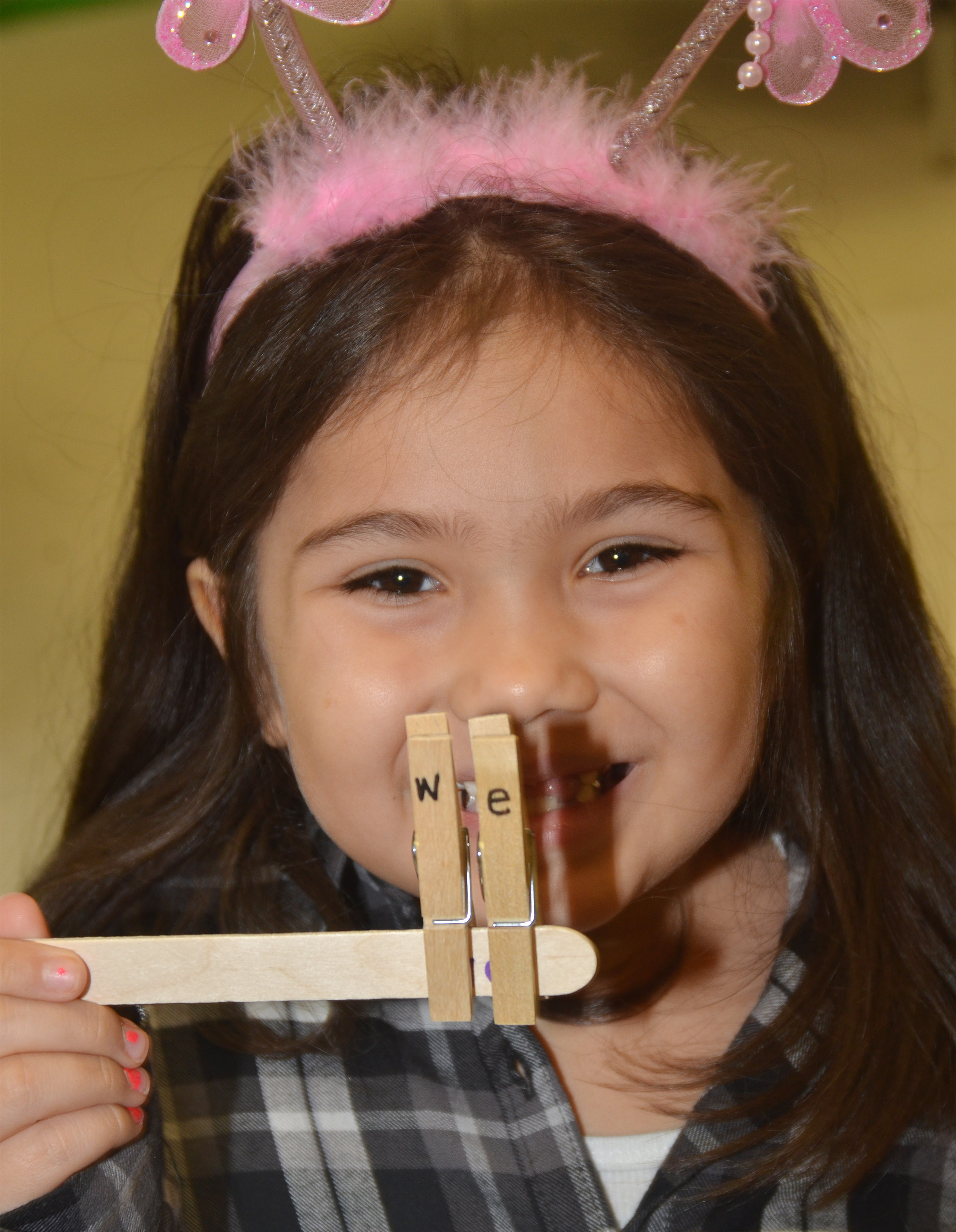 "CES kindergartener Hannah Matias spells ""we"" with clothes pins."