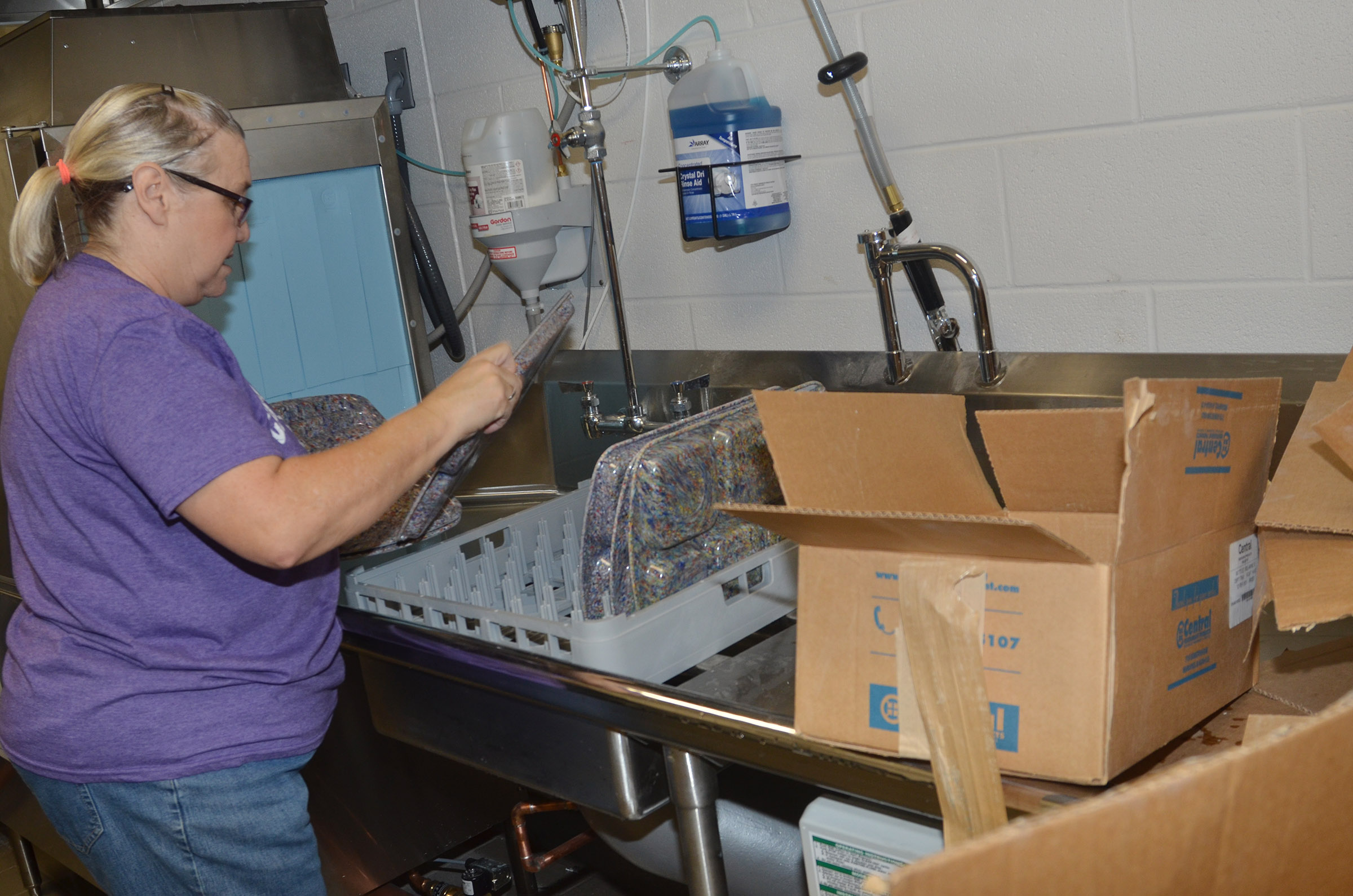 CES cafeteria worker Anita Haulk washes new trays.