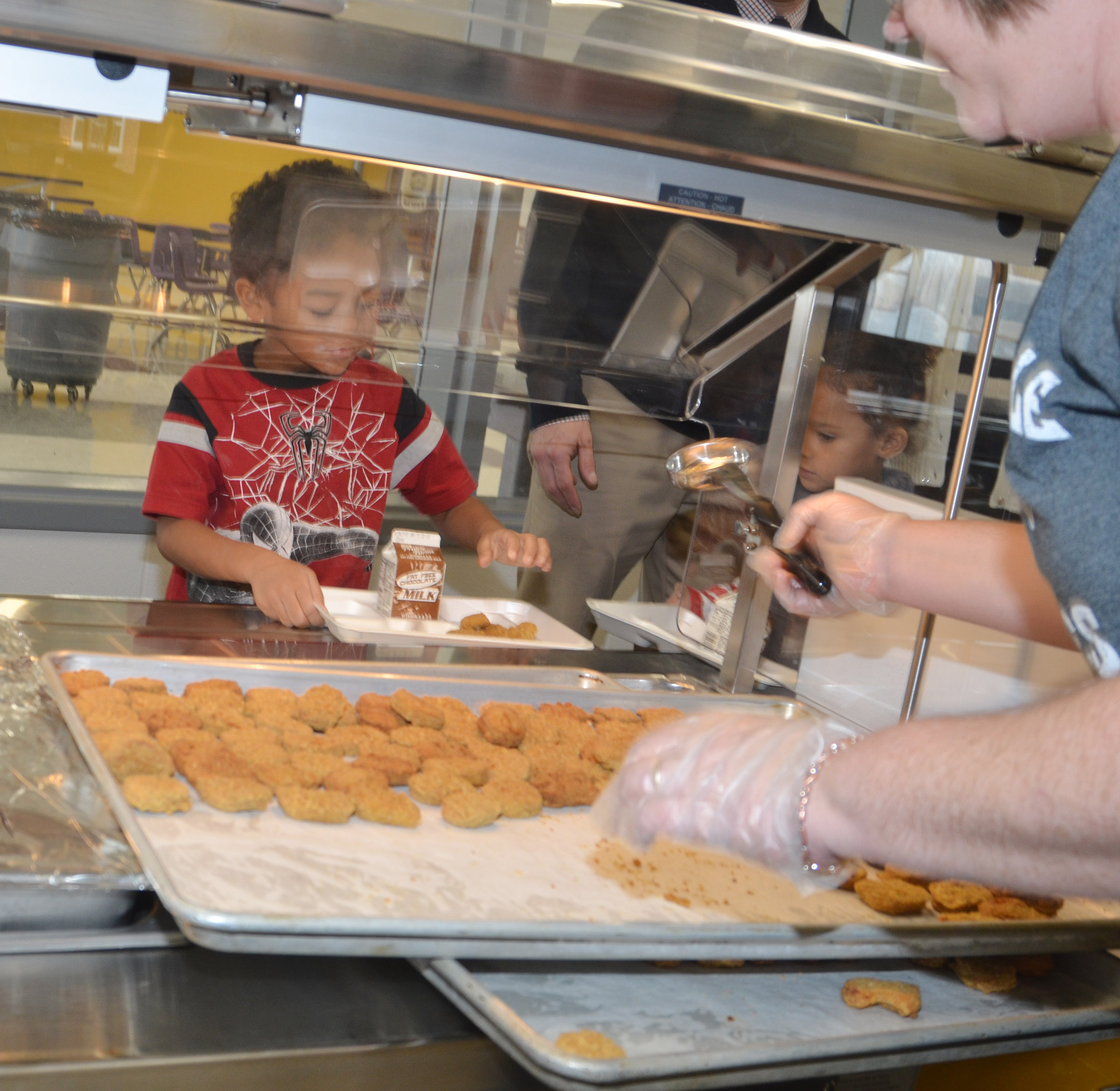 CES kindergartener Tyler Branch is served chicken nuggets as he uses the school's new cafeteria for the first time.