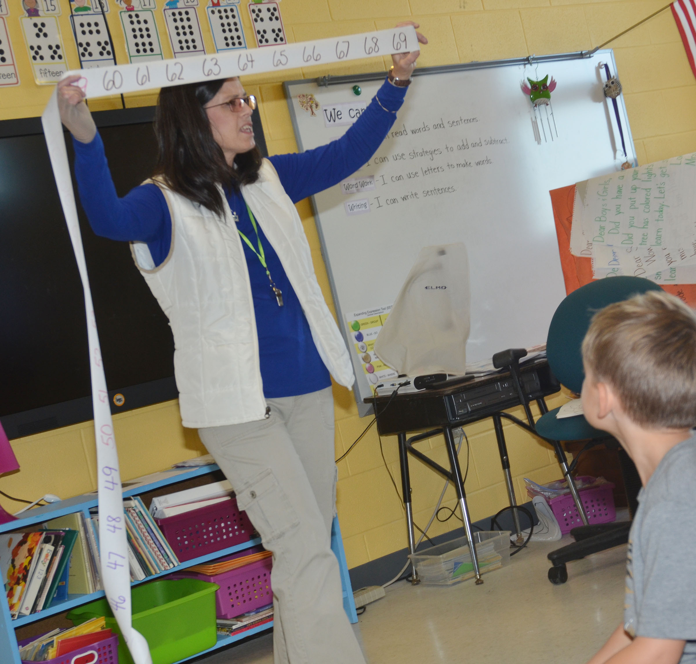 CES first-grade teacher Shirley Cox helps her students count from 60 to 69.
