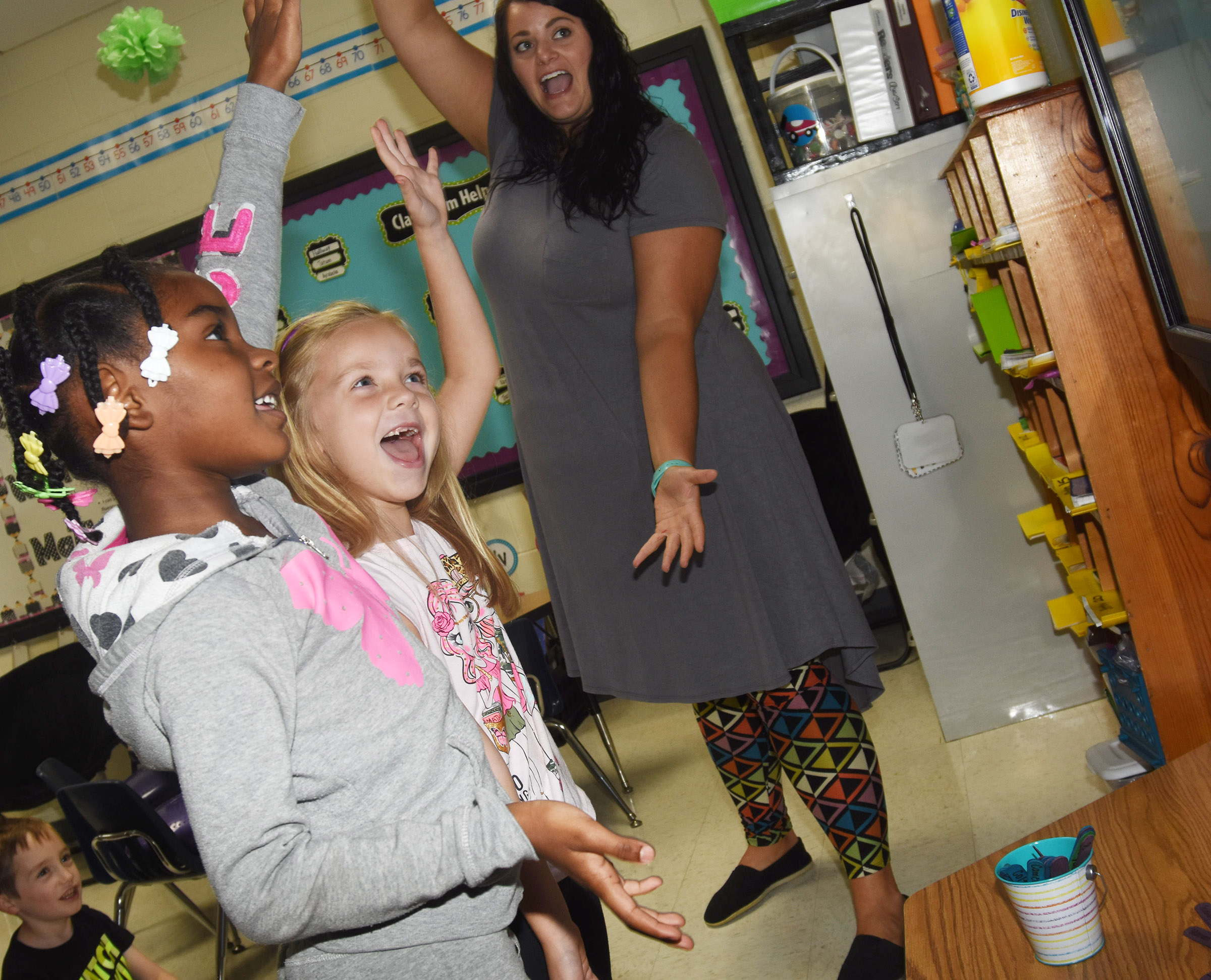 CES first-graders Mariah Harris, at left, and Trinidy Gribbins play an air punctuation game with teacher Miriah Cox.