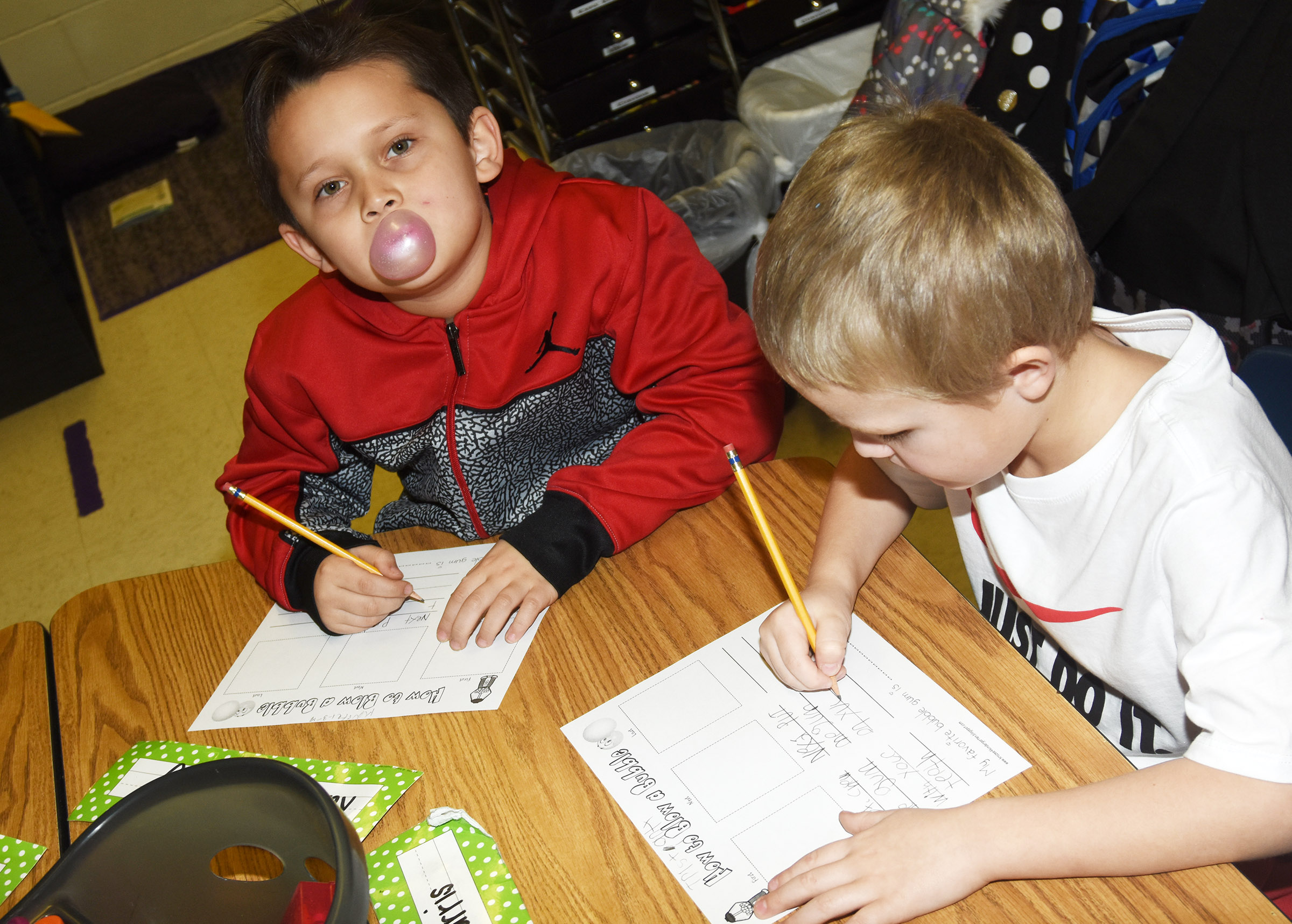 CES first-grader Karter Young, at left, blows a bubble as he and classmate Tristian Harris write the steps to blowing the perfect bubble.