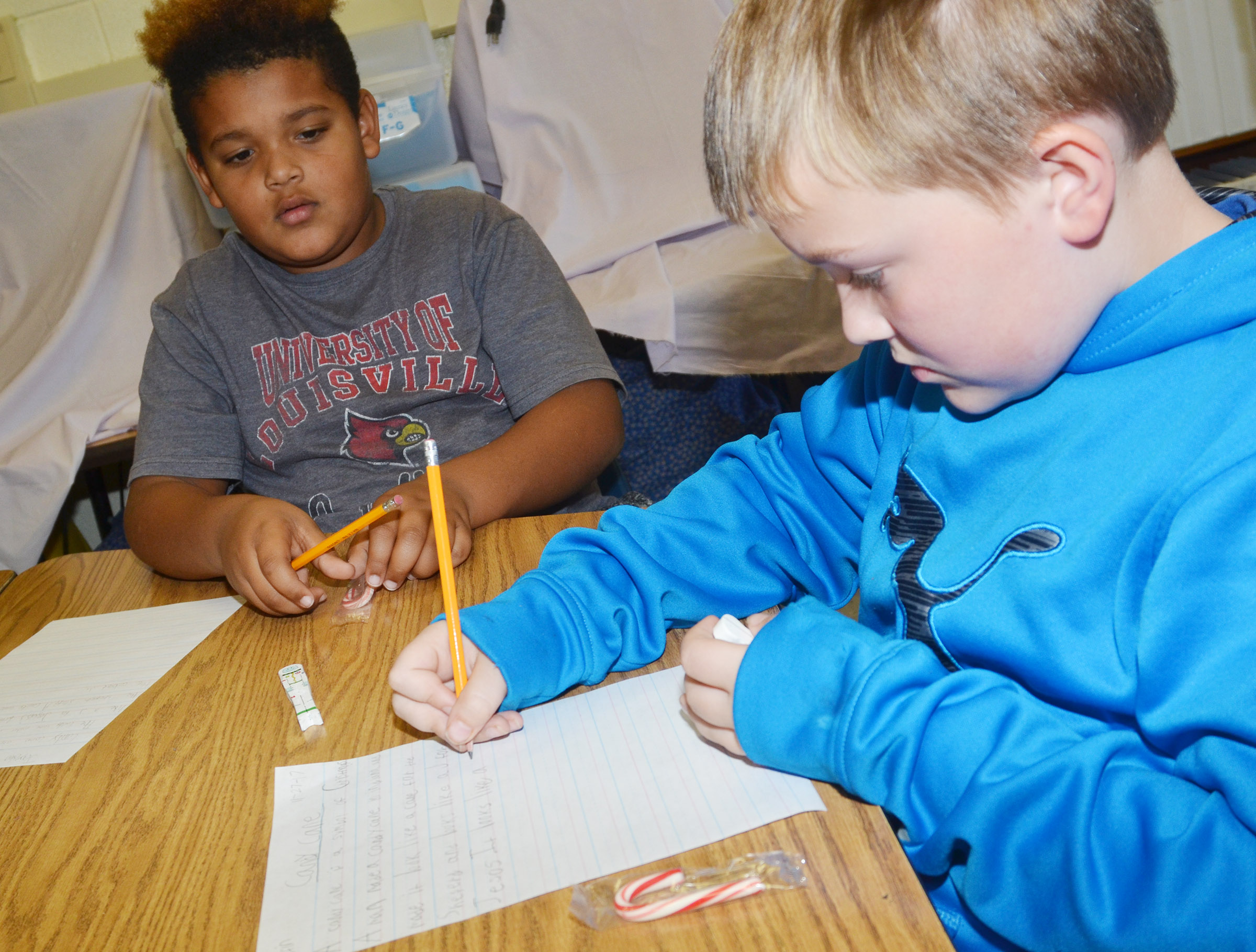 CES third-graders Jayden Moore, at left, and Griffin Skaggs write about candy canes.