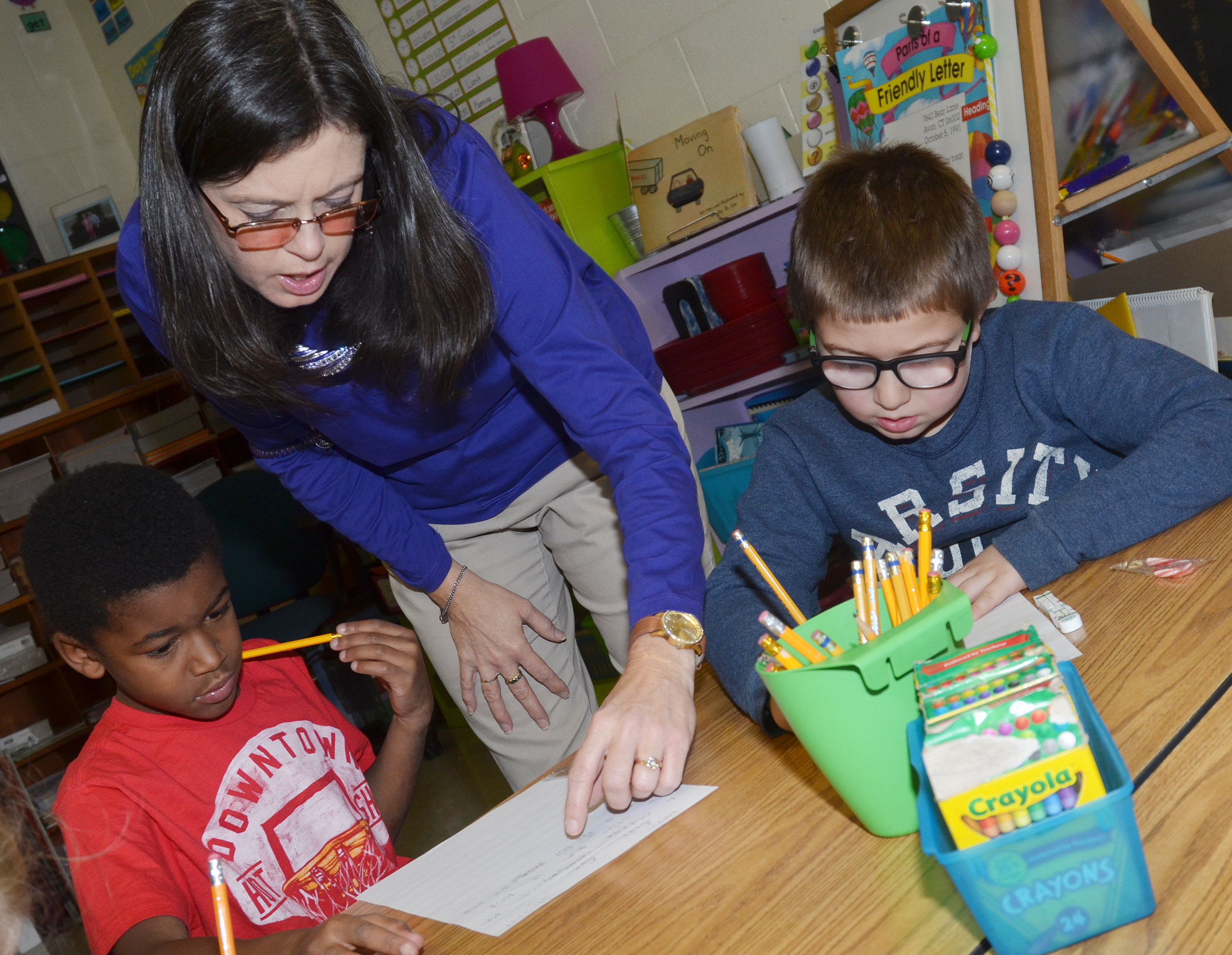 CES writing teacher Shirley Cox helps third-graders Kae'vin Spaulding, at left, and Camron Bryant with their writing.