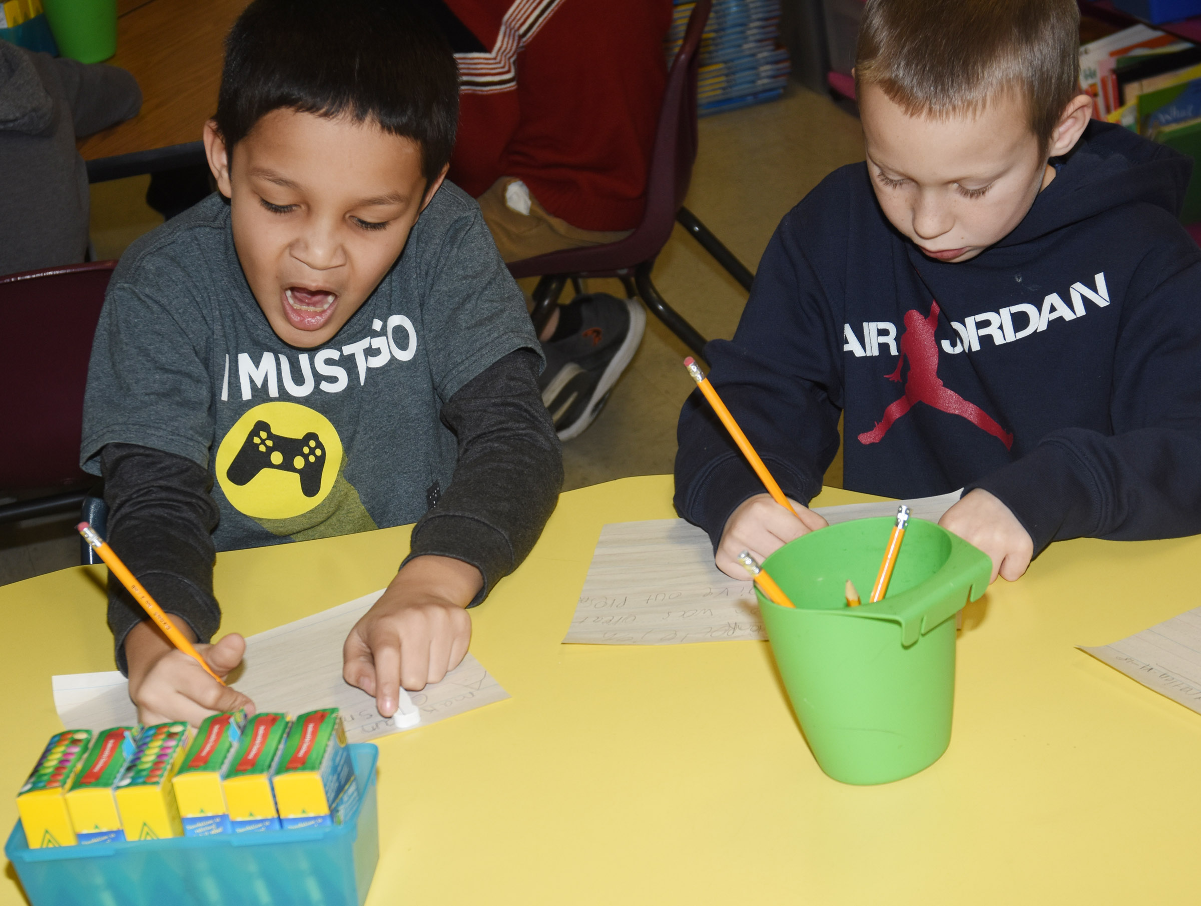 CES second-graders Makyian Bridgewater, at left, and Raleigh Spencer write about their Christmas vacations.