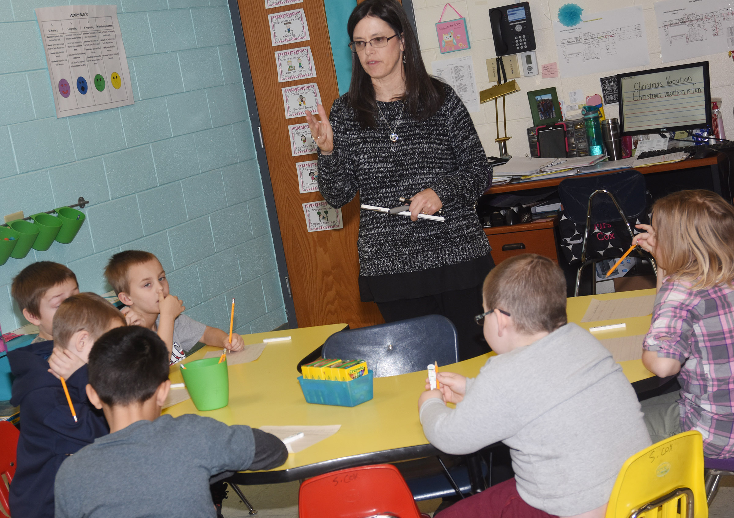 CES writing teacher Shirley Cox talks to her students about the proper way to write a sentence.